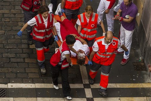 Medical assistants help a participant injured during the running of the bulls, at the San Fermin festival, in Pamplona, Spain, Tuesday.