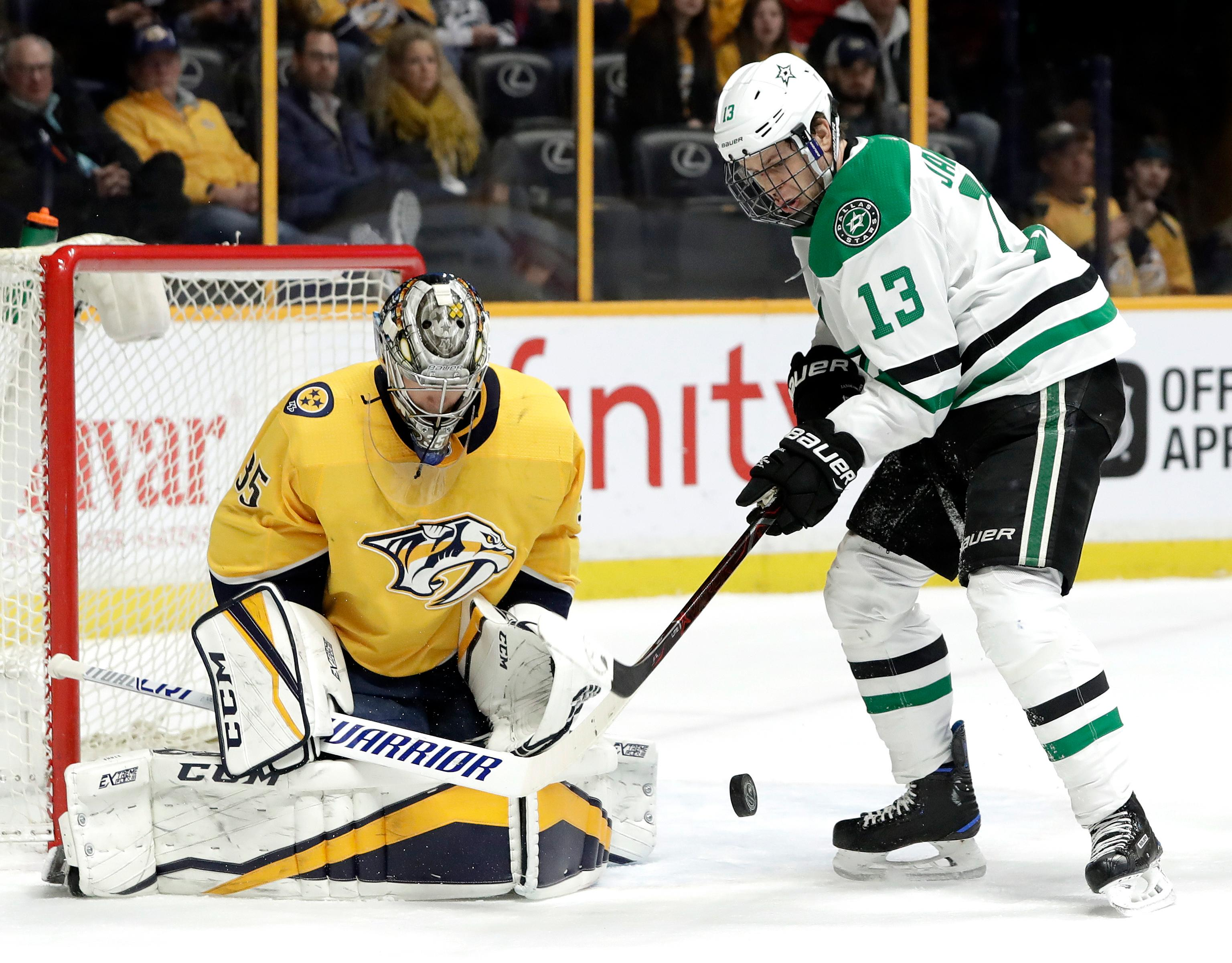 Dallas Stars center Mattias Janmark (13), of Sweden, reaches for the rebound after Nashville Predators goalie Pekka Rinne (35), of Finland, blocked a shot in the first period of an NHL hockey game Tuesday, March 6, 2018, in Nashville, Tenn. (AP Photo/Mark Humphrey)