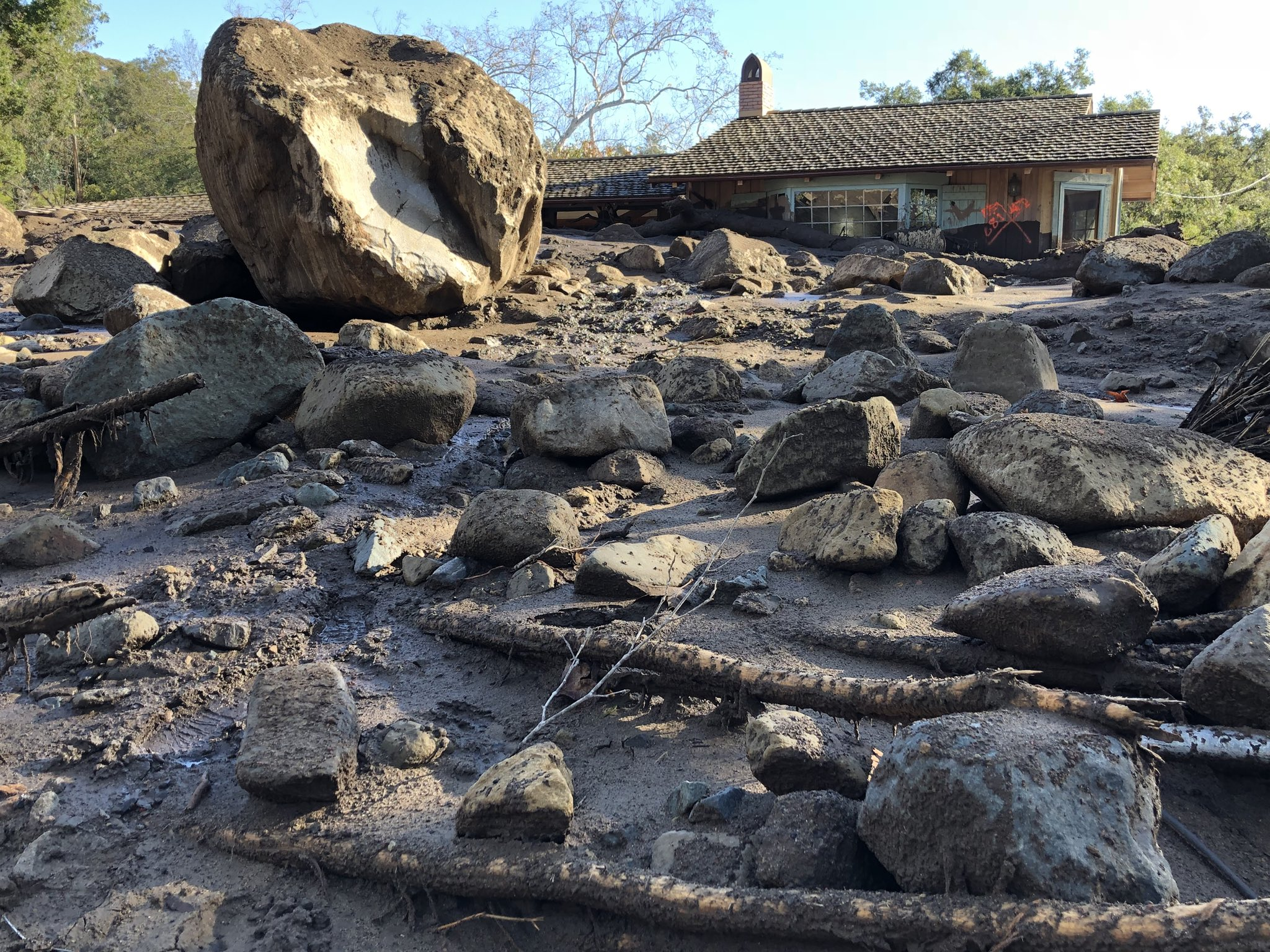 Destroyed homes dot the landscape along San Ysidro Creek near East Valley Road in Montecito. Runoff from heavy rain early Tuesday brought boulders, mudflow, and debris. (Photo & Caption: Mike Eliason, Santa Barbara County Fire Dept.)