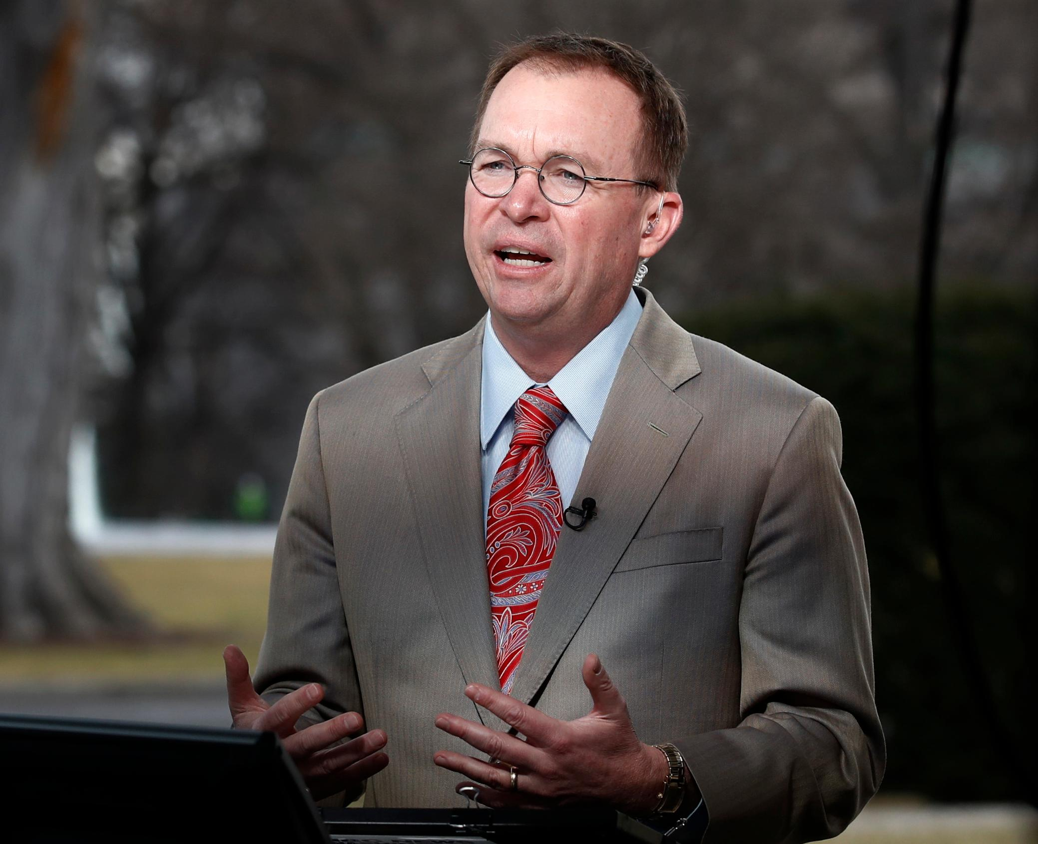 File- This Jan. 22, 2018, file photo shows Director of the Office of Management and Budget Mick Mulvaney talking during a television interview outside the White House in Washington. Mulvaney, the former tea party congressman who runs the White House budget office, said Sunday, Feb. 11, 2018, that Trump's new budget, if implemented, would tame the deficit over time, though unlike last year's submission, it wouldn't promise to balance the federal ledger eventually. (AP Photo/Carolyn Kaster, File)