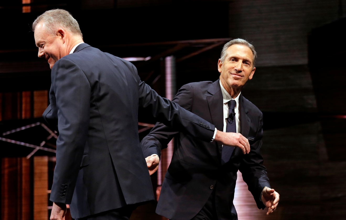 Starbucks CEO Howard Schultz, right, heads off the stage after introducing President and Chief Operating Officer Kevin Johnson at the company's annual shareholders meeting, Wednesday, March 22, 2017, in Seattle. Johnson takes over as CEO from Schultz, who will become executive chairman, in April. (AP Photo/Elaine Thompson)