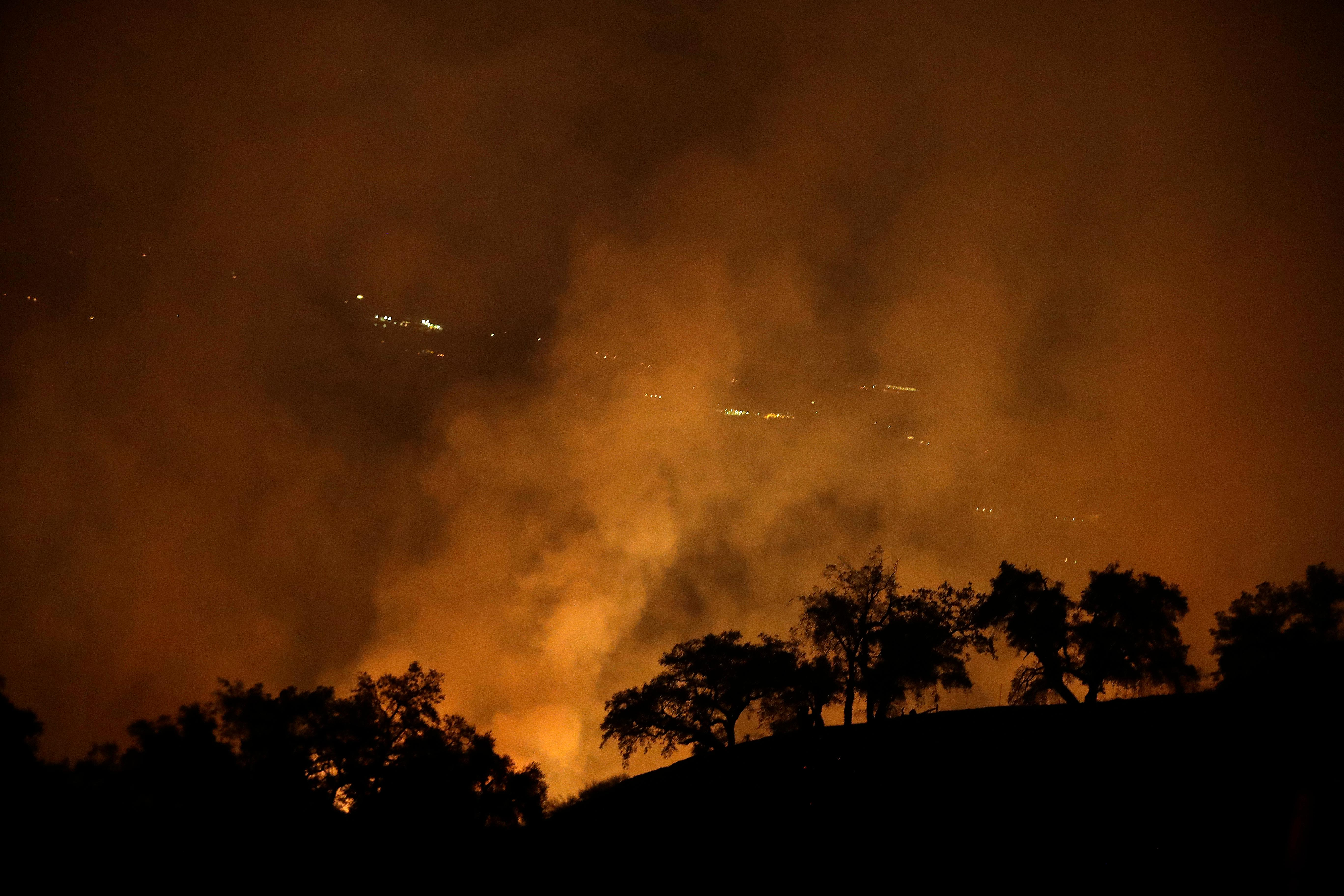 A wildfires creates an orange glow in a view from a hilltop Friday, Oct. 13, 2017, in Geyserville, Calif. (AP Photo/Marcio Jose Sanchez)