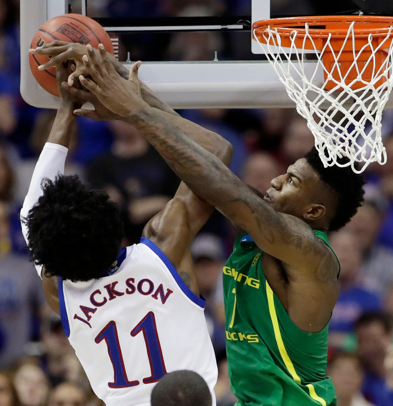 Oregon forward Jordan Bell, right, tries to block a shot by Kansas guard Josh Jackson (11) during the second half of the Midwest Regional final of the NCAA men's college basketball tournament, Saturday, March 25, 2017, in Kansas City, Mo. (AP Photo/Charlie Riedel)