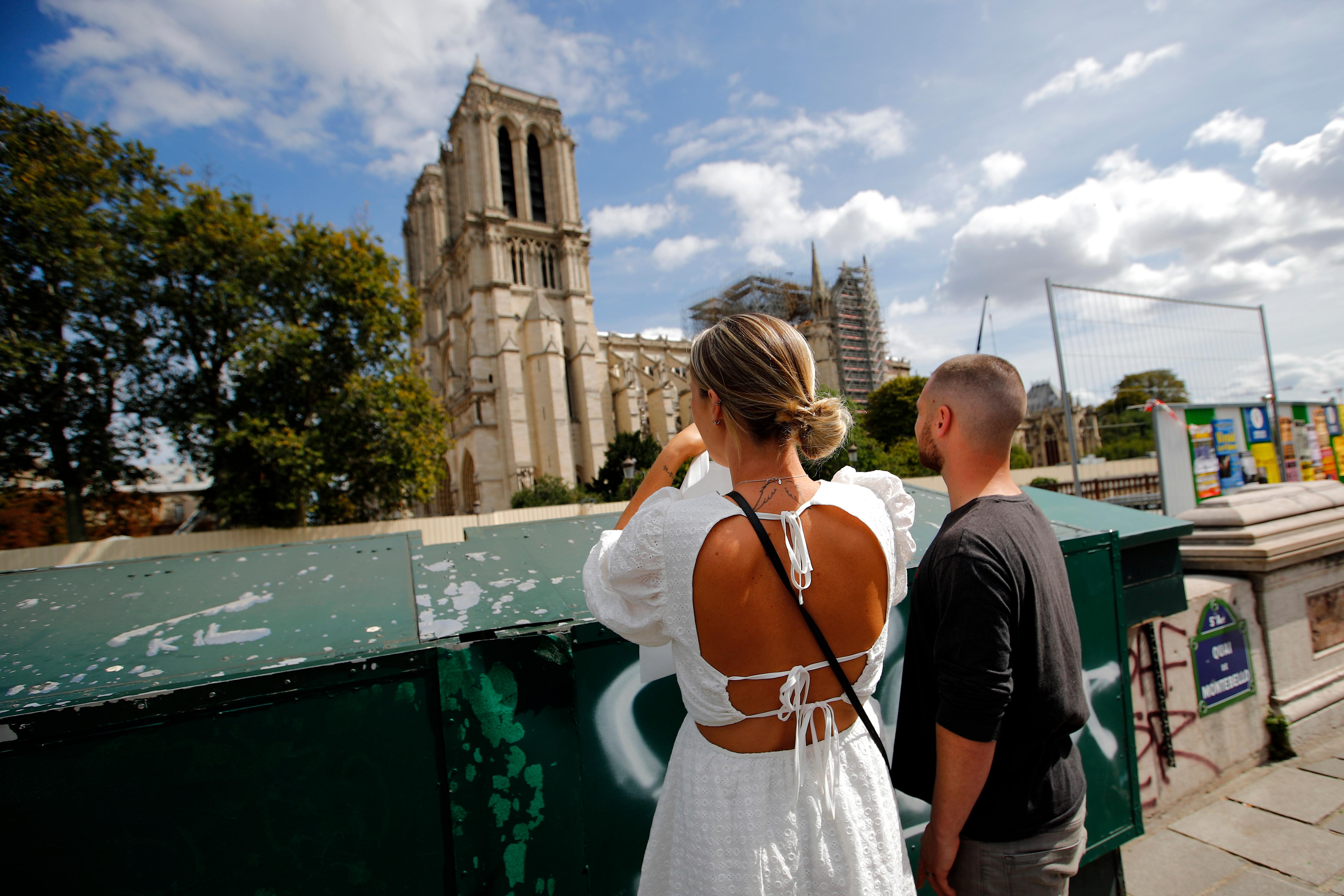 Tourists take a look around the Notre Dame Cathedral ahead of the start of a massive lead decontamination in Paris, Friday, Aug. 16, 2019. (AP Photo/Francois Mori)
