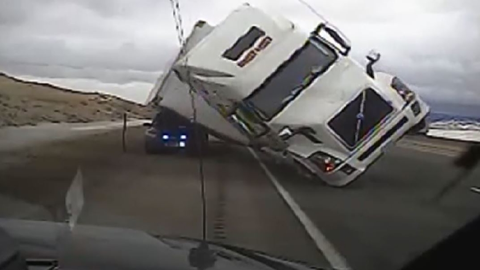 watch  semi blows over  crushes patrol car on wyoming highway