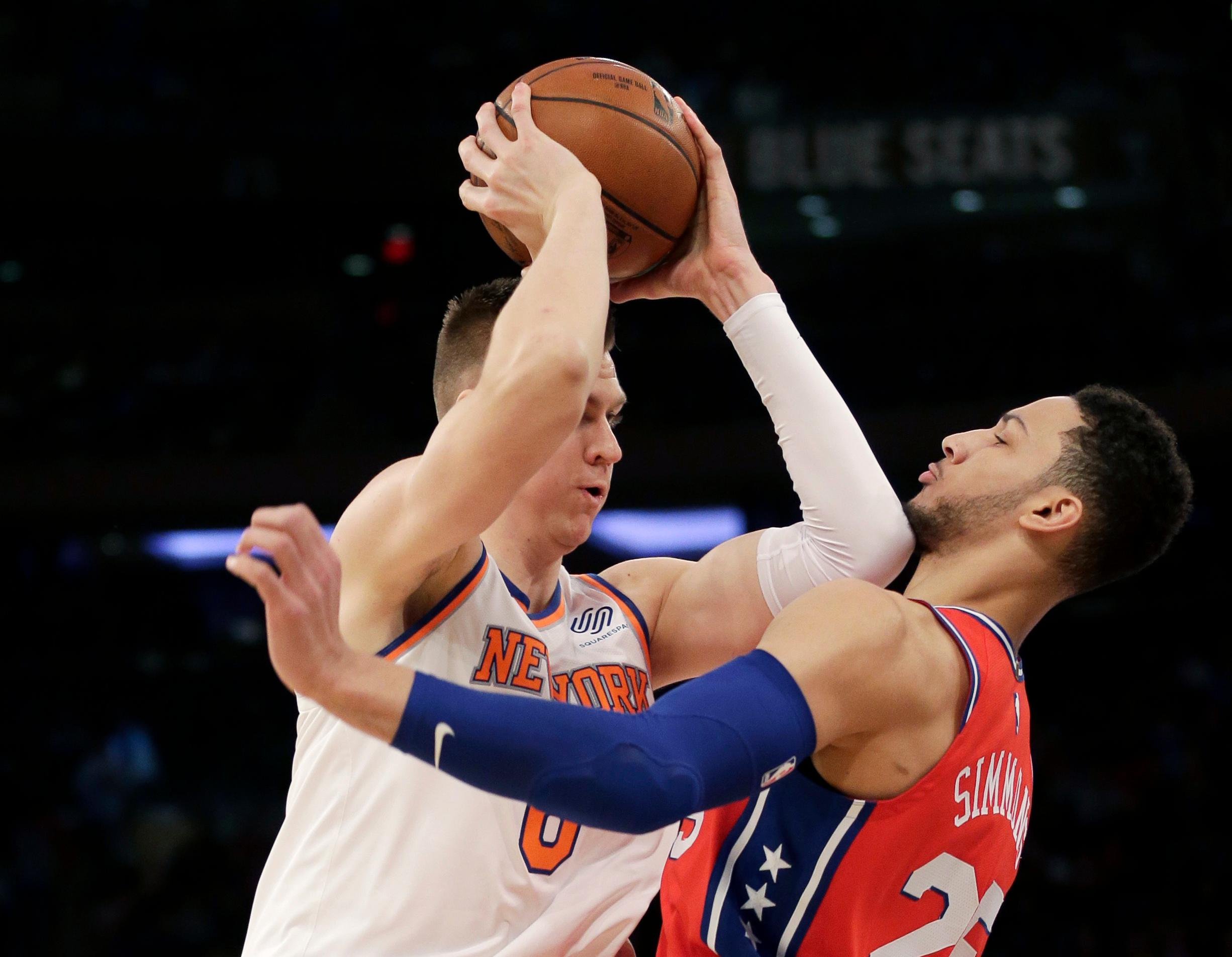 New York Knicks' Kristaps Porzingis, left, tries to move past Philadelphia 76ers' Ben Simmons during the first half of the NBA basketball game, Monday, Dec. 25, 2017, in New York. (AP Photo/Seth Wenig)
