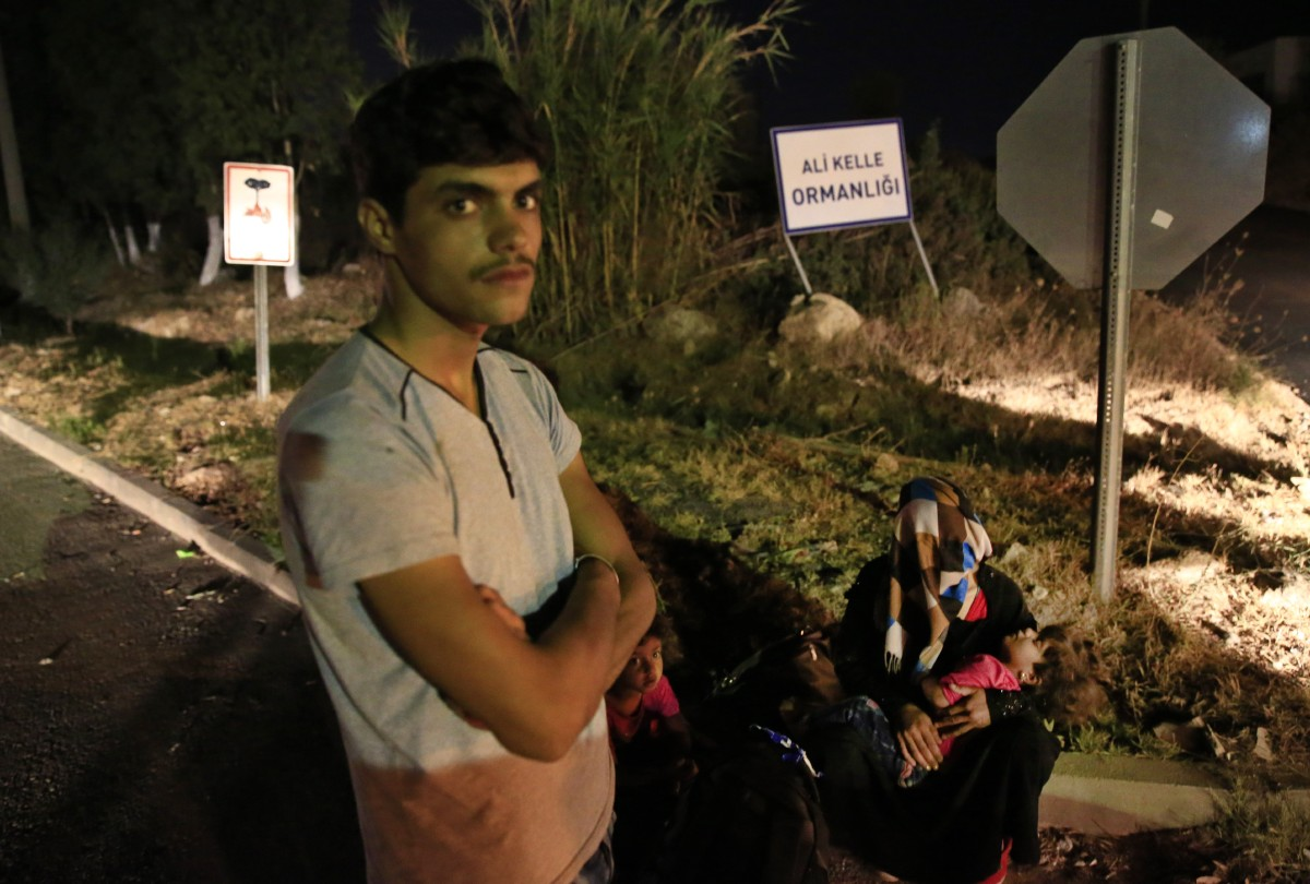 Migrants from Syria wait as they try to head to the meeting point in order to try to cross with boats to the nearby Greek island of Kos, at the coastal town of Bodrum, Turkey, early Saturday, Aug. 15, 2015. The town of Bodrum, a magnet for wealthy tourists, is these days drawing plenty of other visitorsó migrants fleeing conflicts in the Middle East and Africa and seeking a better life in Europe. At its closest point, the Greek island of Kos is only 4 kilometers (2.5 miles) from Turkey and migrants, mostly from Syria, but also from Afghanistan, Iran and African nations often try to cross in groups upward of eight people in small inflatable plastic boats meant for a maximum of four, powered by tiny electric outboard motors and plastic paddles. (AP Photo/Lefteris Pitarakis)