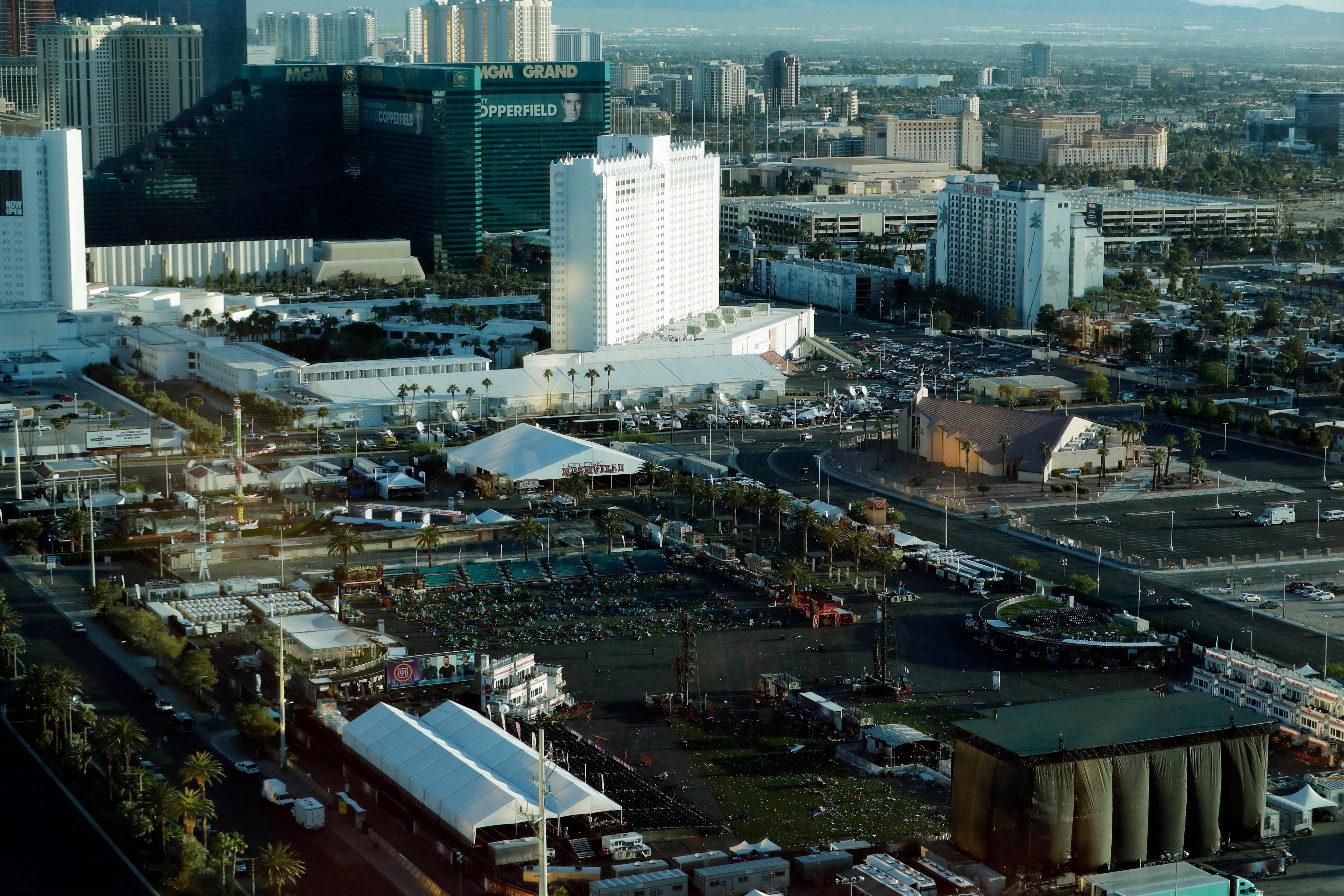 Debris litters a festival grounds across the street from the Mandalay Bay resort and casino Tuesday, Oct. 3, 2017, in Las Vegas. Authorities said Stephen Craig Paddock broke windows on the casino and began firing with a cache of weapons, killing dozens and injuring hundreds at a music festival at the grounds.  (AP Photo/Marcio Jose Sanchez)