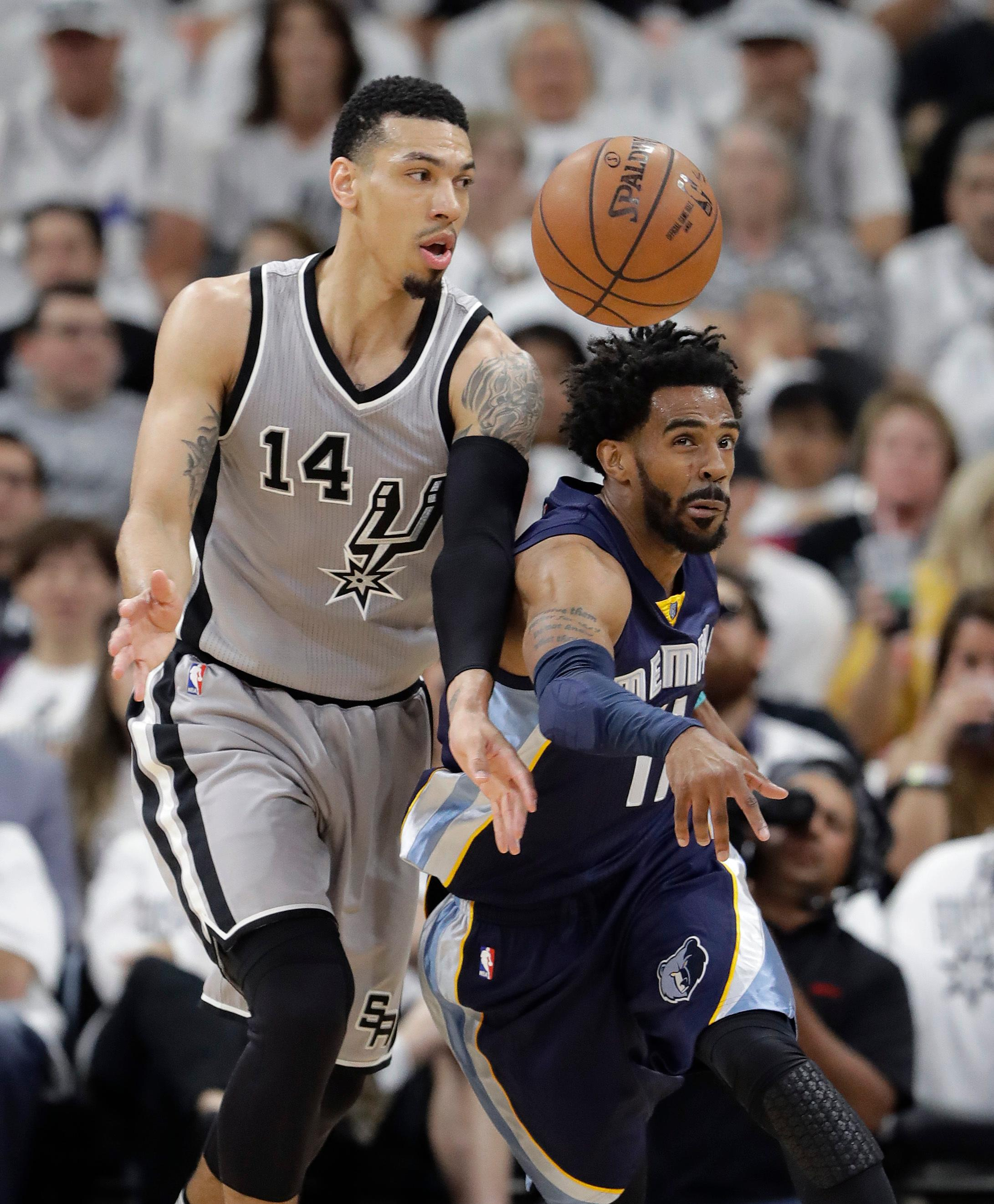 Memphis Grizzlies guard Mike Conley (11) knocks the ball away from San Antonio Spurs guard Danny Green (14) during Game 1 of a first-round NBA basketball playoff series, Saturday, April 15, 2017, in San Antonio. (AP Photo/Eric Gay)