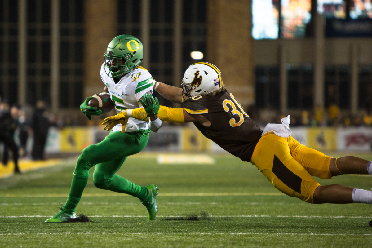 Oregon wide receiver Taj Griffin (#5) shakes a tackle from Wyoming linebacker Logan Wilson (#30). The Oregon Ducks recorded their first road win under head coach Willie Taggart with their 49-13 victory over the Wyoming Cowboys on a cold night at War Memorial Stadium in Laramie, Wyoming.  Photo by Austin Hicks, Oregon News Lab