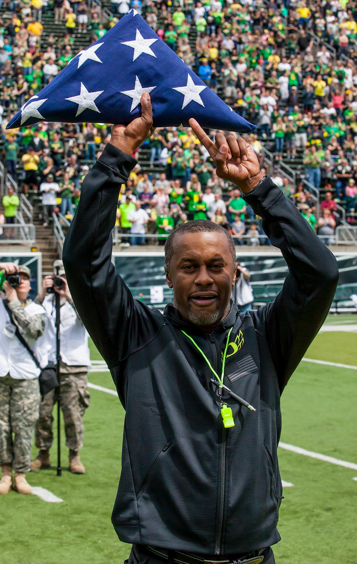 Head Coach Willie Taggart displays an American flag presented to him by service members of the United States Military during half time. The 2017 Oregon Ducks Spring Game provided fans their first glimpse at the team under new Head Coach Willie Taggart's direction. Team Free defeated Team Brave 34-11 on a sunny dat at Autzen Stadium in Eugene, Oregon. Photo by Ben Lonergan, Oregon News Lab