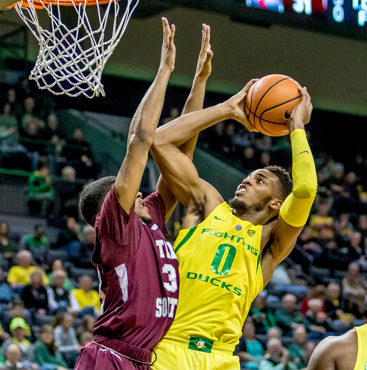 The Duck's Troy Brown (#0) makes a throw for the basket as the Tiger's Robert Lewis (#33) tries to block the shot. The Oregon Ducks defeated Texas Southern Tigers 74-68. The Ducks are now 7-3 overall in the Pac-12. Photo by August Frank. Oregon News Lab
