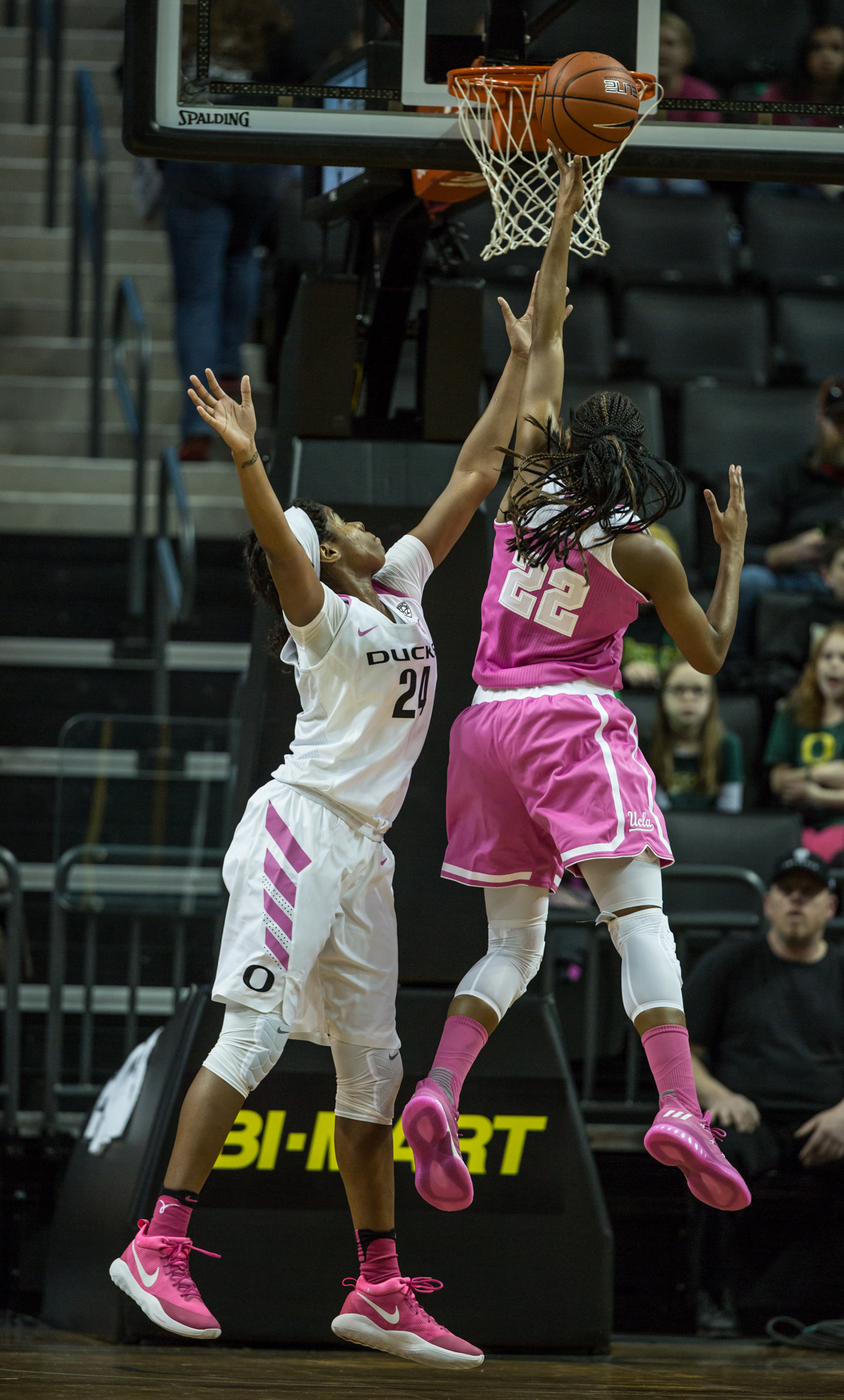UCLA Bruins guard Kennedy Burke (#22) shoots through the arms of Oregon Ducks defender Ruthy Hebard (#24). The Oregon Ducks defeated the No. 15 UCLA Bruins 84-75 Friday evening at Matthew Knight Arena in Eugene, Oregon.  Photo by Austin Hicks, Oregon News Lab