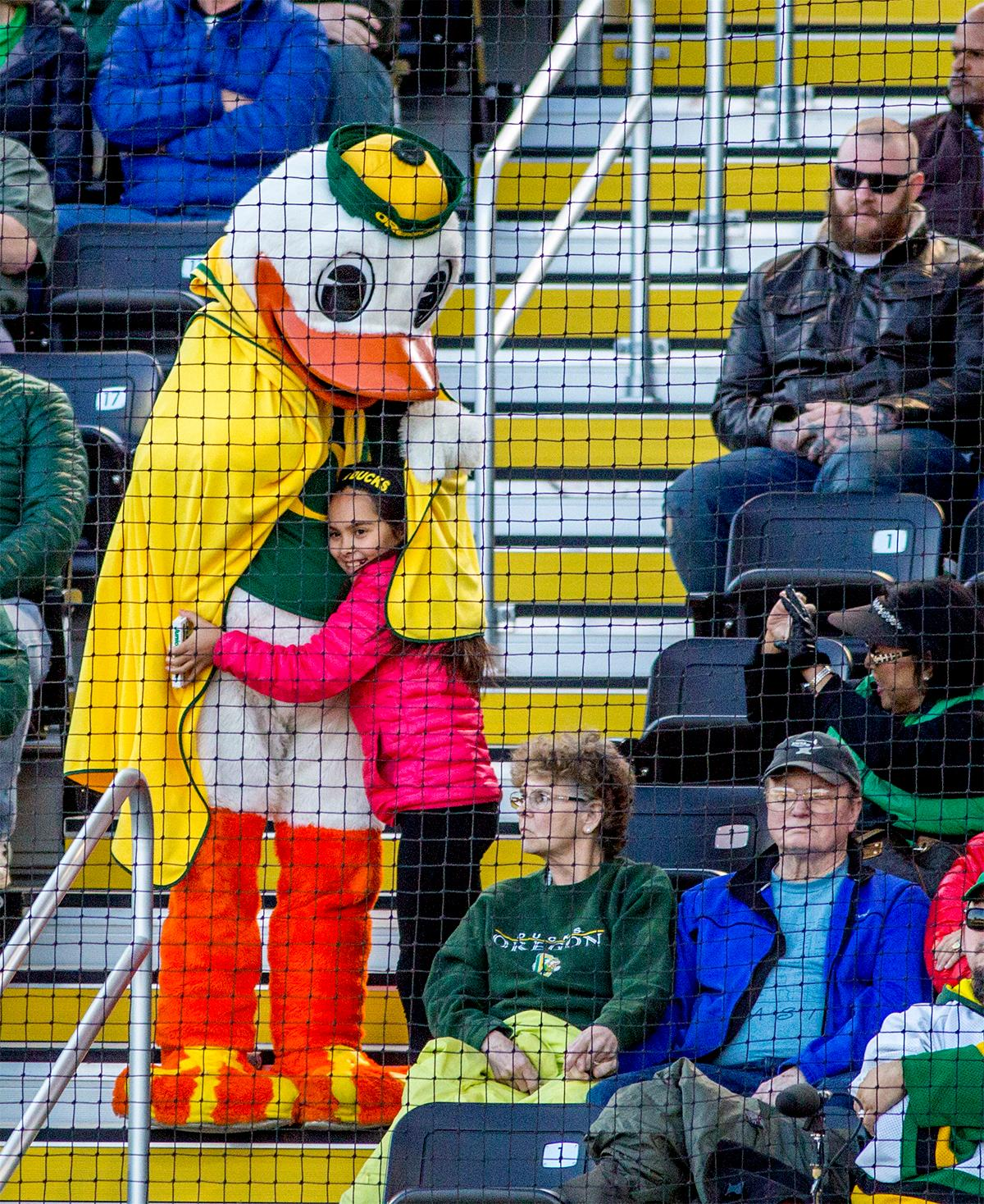 The Duck gives a child a hug while adorned in a cape. The Oregon Ducks defeated the Oregon State Beavers 8-0 in game one of the three-game Civil War series on Friday night at Jane Sanders Stadium. The game was 0-0 until Gwen Svekis (#21) hit a solo home run in the fourth inning. Mia Camuso hit a grand slam in the fifth inning, ending the game for the Ducks by mercy rule. With tonight's victory, the Ducks are 39-6 and 12-6 in Pac-12 play. Photo by August Frank, Oregon News Lab
