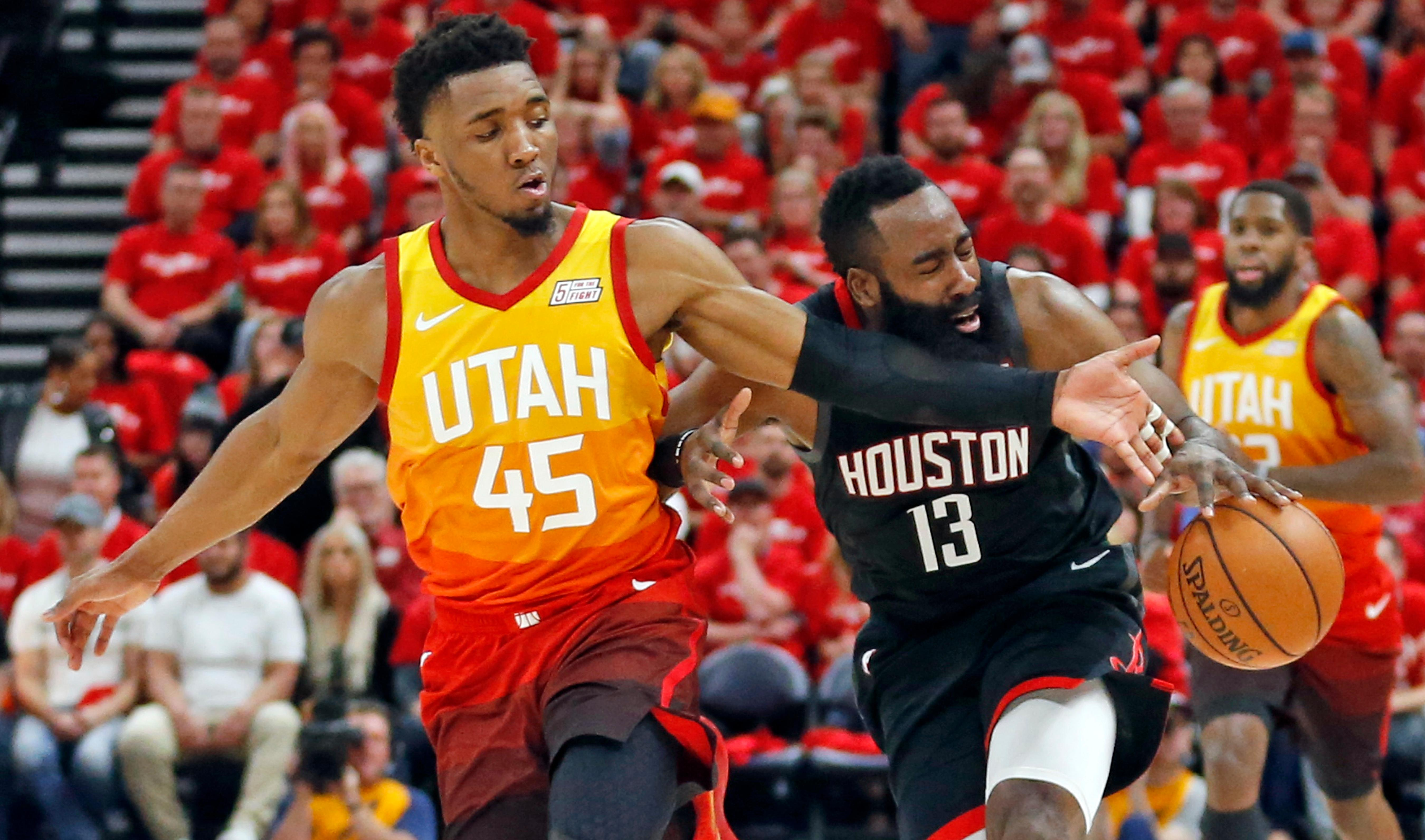 Utah Jazz guard Donovan Mitchell (45) defends against Houston Rockets guard James Harden (13) as he drives up court in the first half during an NBA basketball game Saturday, April 20, 2019, in Salt Lake City. (AP Photo/Rick Bowmer)