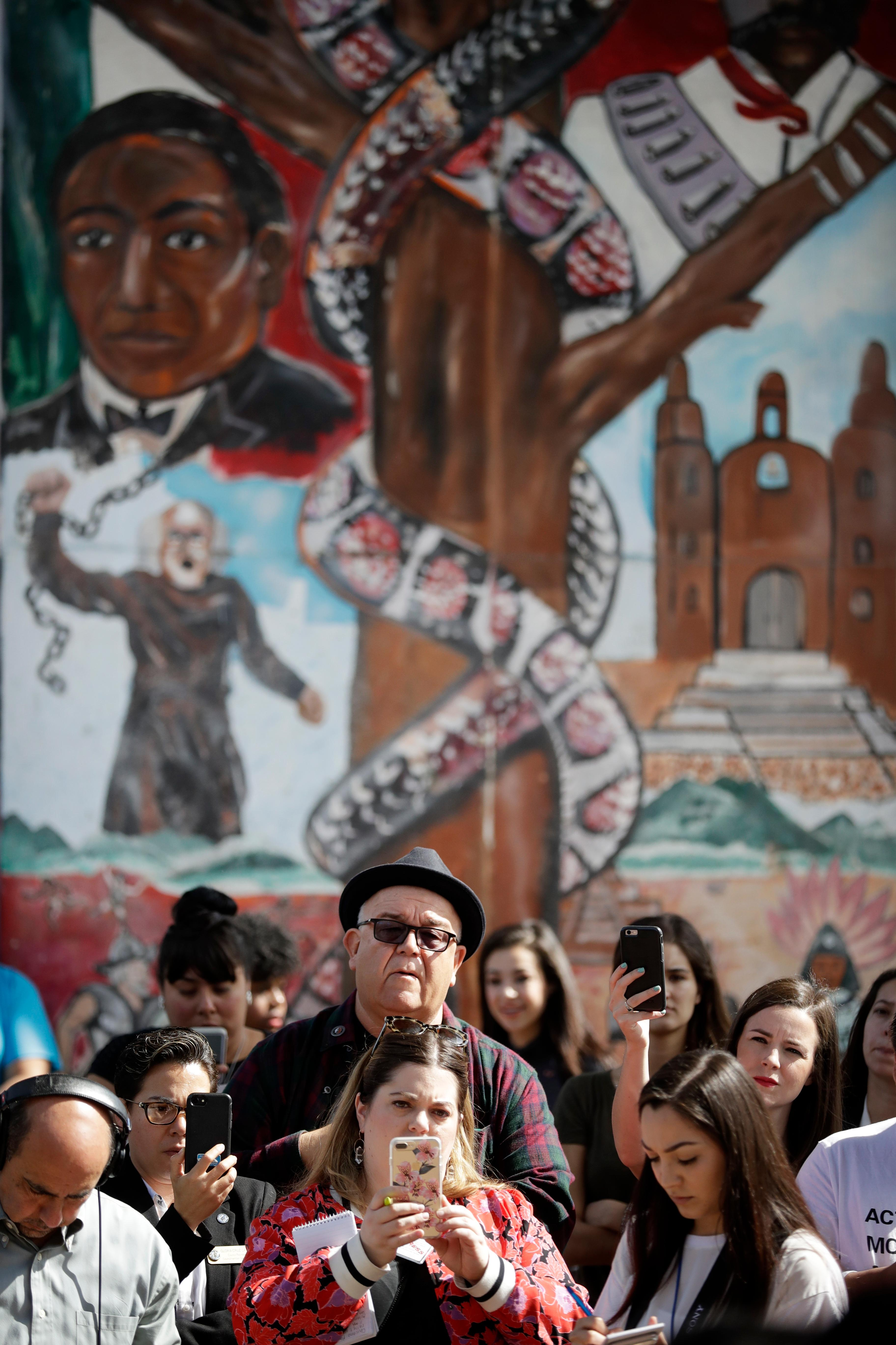 People look on in front of a mural depicting heroes of the Mexican revolution during a rally against a scheduled upcoming visit to the area by President Donald Trump Monday, March 12, 2018, in San Diego. Trump is scheduled to visit San Diego Tuesday, setting foot in California for his first time as president. (AP Photo/Gregory Bull)