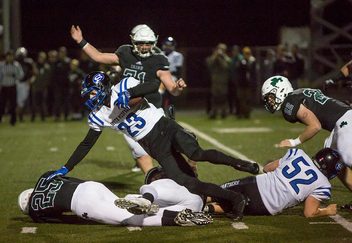 South Medford Panther Chase Cota (#23) is brought down after attempting to break through Sheldon's defense. The South Medford Panthers defeated the Sheldon Irish 31 – 14 at Sheldon High School on Friday, October 20. Photo by Kit MacAvoy, Oregon News Lab
