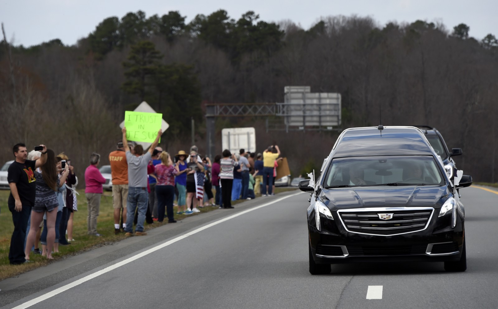 People watch as the hearse carrying the body of Billy Graham leaves Hickory, N.C., as it drives toward the Billy Graham Library Saturday, Feb. 24, 2018. Graham's body was brought to his hometown of Charlotte on Saturday, Feb. 24, as part of a procession expected to draw crowds of well-wishers. (Kathy Kmonicek/pool photo)