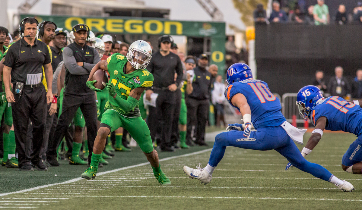 Oregon wide receiver Dillon Mitchell (#13) dodges defenders during a run up the sideline. The Boise State Broncos defeated the Oregon Ducks 38 to 28 in the 2017 Las Vegas Bowl at Sam Boyd Stadium in Las Vegas, Nevada on Saturday December 17, 2017. The Las Vegas Bowl served as the first test for Oregon's new Head Coach Mario Cristobal following the loss of former Head Coach Willie Taggart to Florida State University earlier this month. Photo by Ben Lonergan, Oregon News Lab