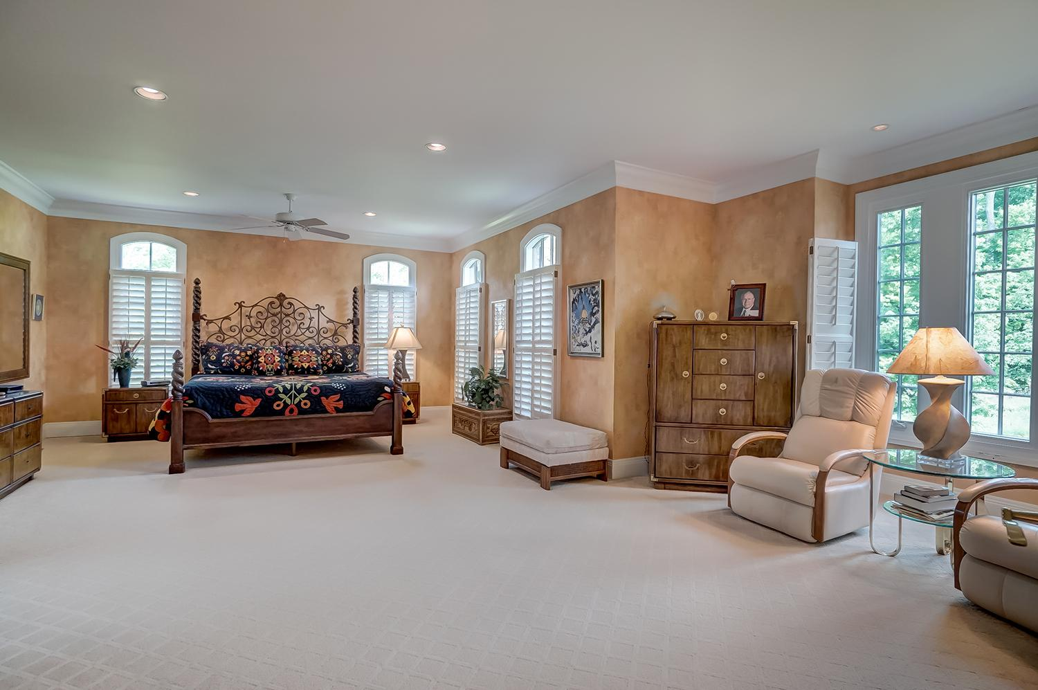 The main first floor master suite has a cozy sitting area, built-in book cases and a fireplace. A thoughtful combination of arched windows, plantation shutters, and crown moldings are conservative, yet impressive. / Image: Wow Video Tours // Published: 6.8.18
