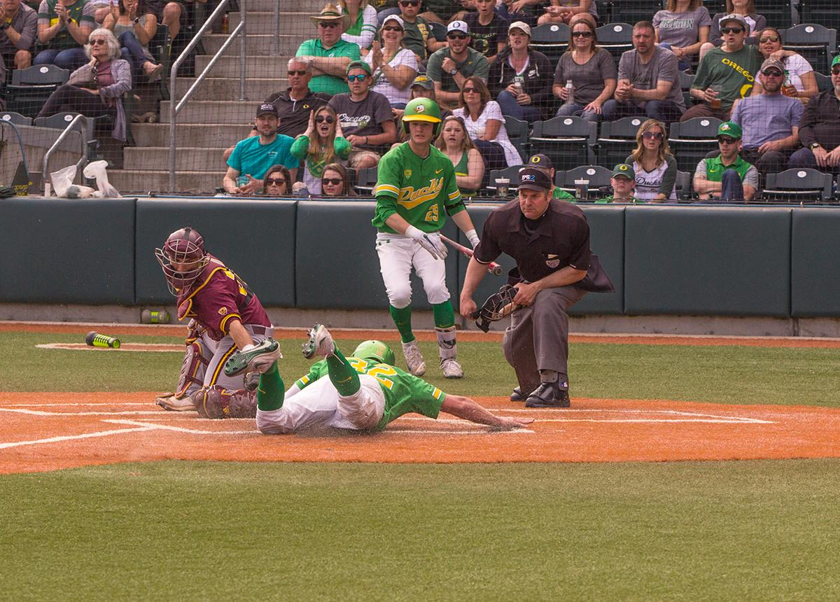 Ducks Jake Bennett(#32) slides into home base for a run attempt. Despite a late comeback, the Ducks fall to Arizona State Sun Devils 4-3 in the second game of a three-game series. Photo by James Wegter, Oregon News Lab