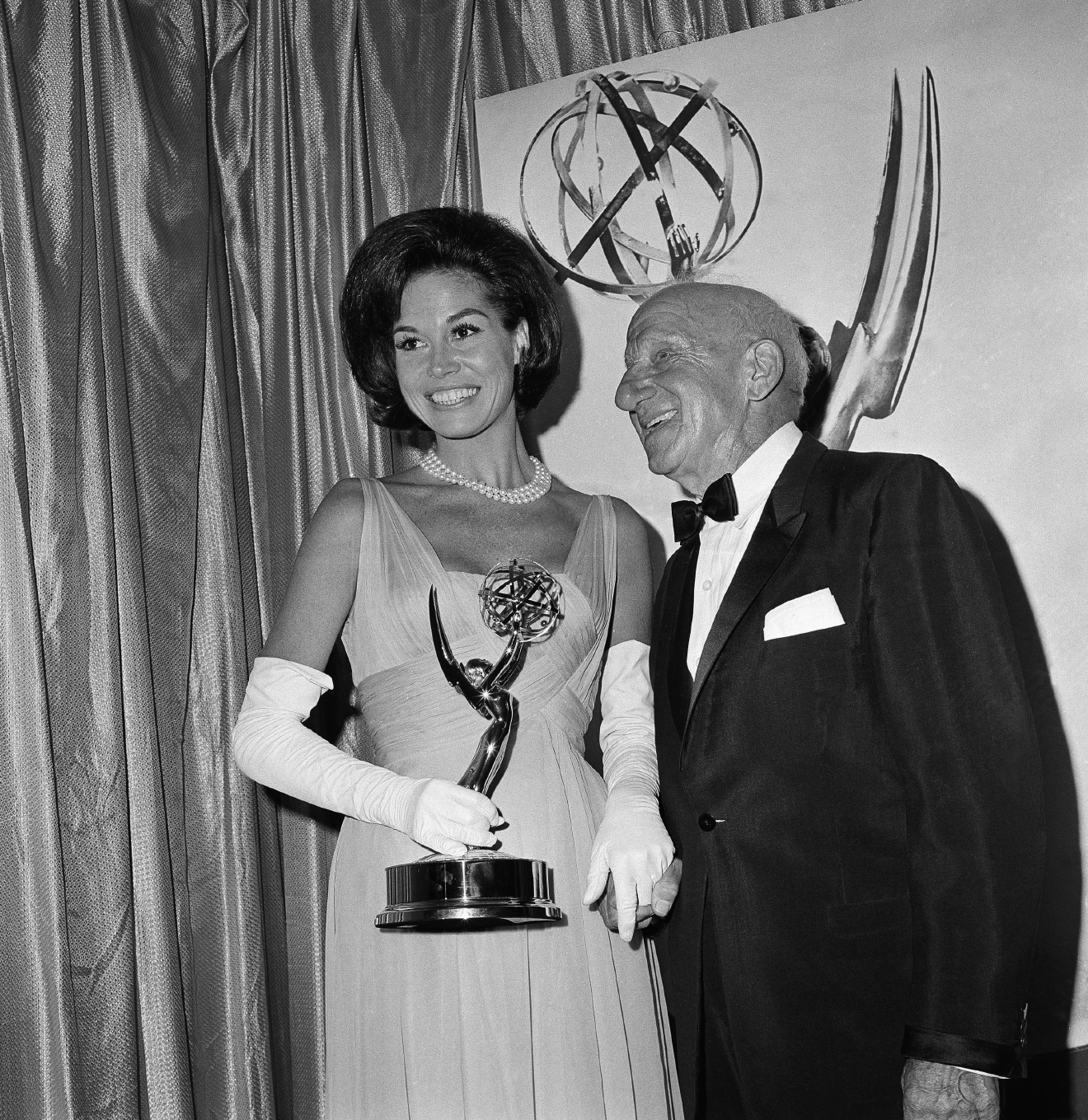 Mary Tyler Moore, who plays Dick Van Dyke's wife on his television show, holds the Television Academy Emmy for outstanding individual achievement awarded to him, in Hollywood, Calif., Sept. 12, 1965. With her is Jimmy Durante who made the presentation. Van Dyke, a previous Emmy winner, was not present at the awards show. (AP Photo/Richard Strobel)