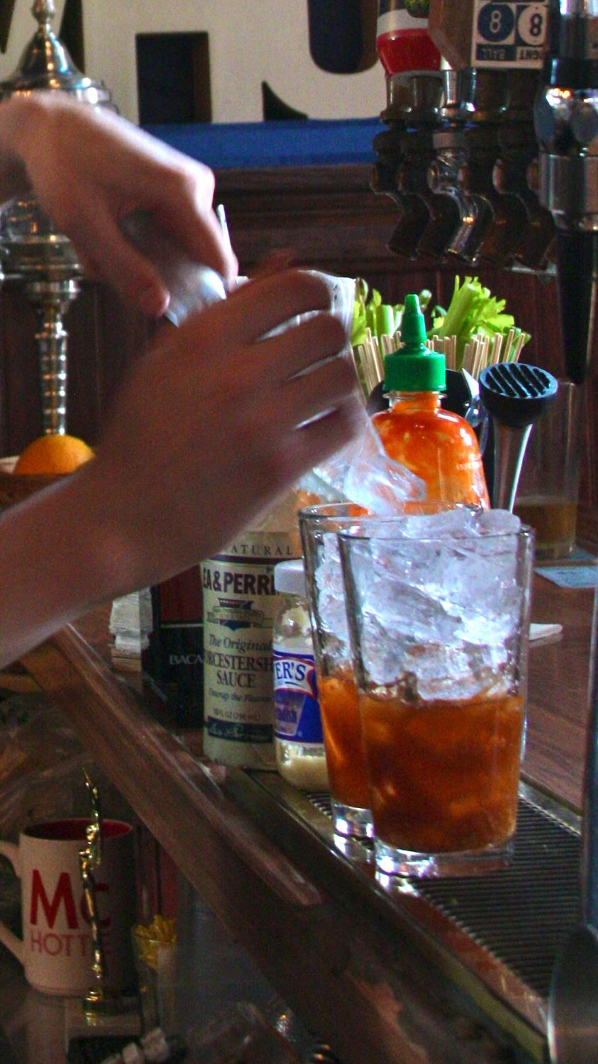 Brandon adds a scoop of ice into the drink with half the Bloody Mary mix already added / Image: Molly Paz