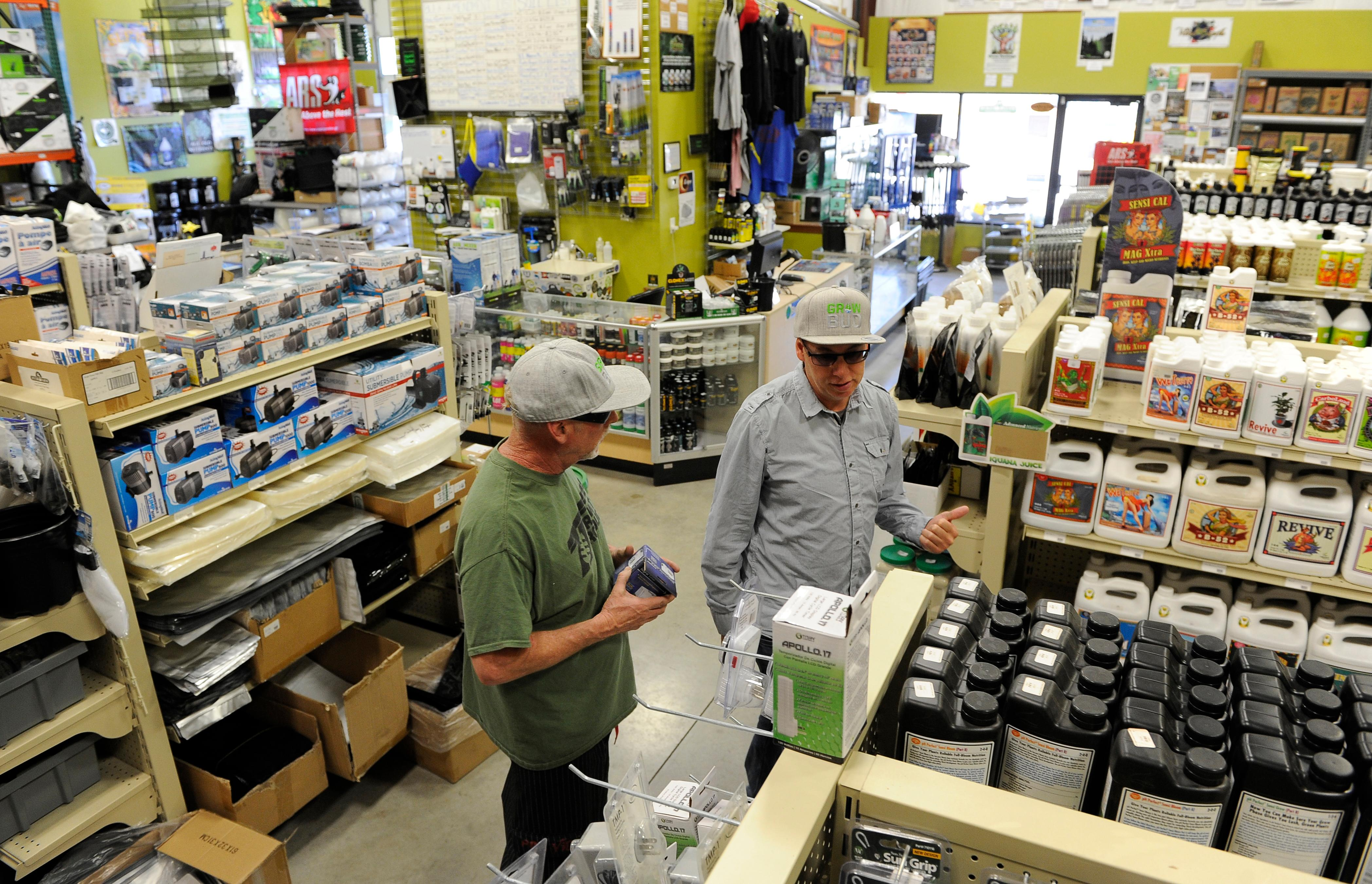 Andy Atkinson / Mail Tribune <br><p>Jamin Giersbach, right, helps a customer inside Rogue Farmers hydroponic store in Talent.</p>