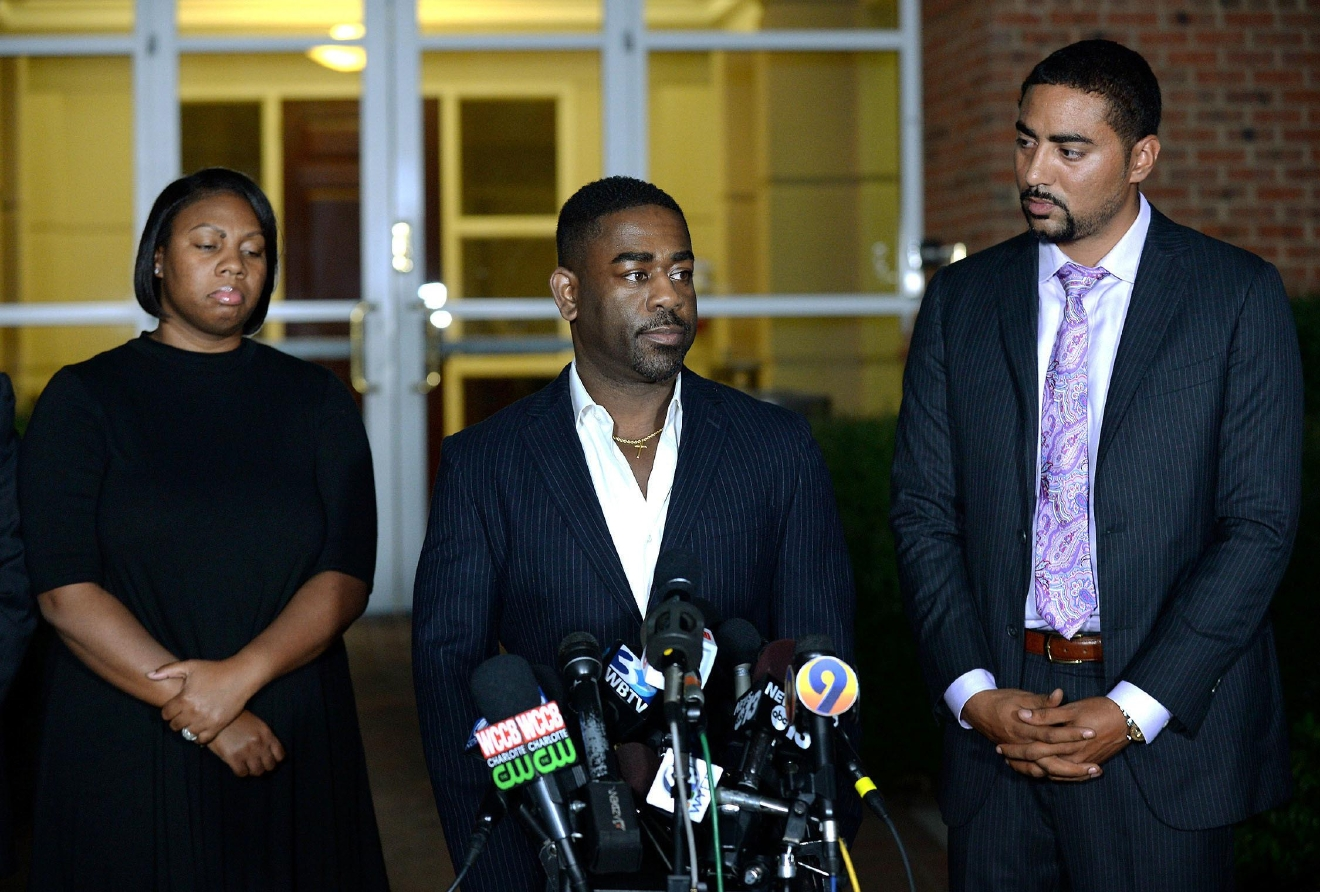 "Rachel, left, and Ray Dotch, center, sister-in-law and brother-in-law to Keith Lamont Scott, give a news conference in Charlotte, N.C., on Saturday, Sept. 24, 2016. At right is the family's attorney, Justin Bamberg. Scott was fatally shot by Charlotte-Mecklenburg Police Officer Brentley Vinson on Tuesday. Dotch objected to reporters' questions about Scott's background, saying he shouldn't have to ""humanize in order for him to be treated fairly."" (Jeff Siner/The Charlotte Observer via AP)"