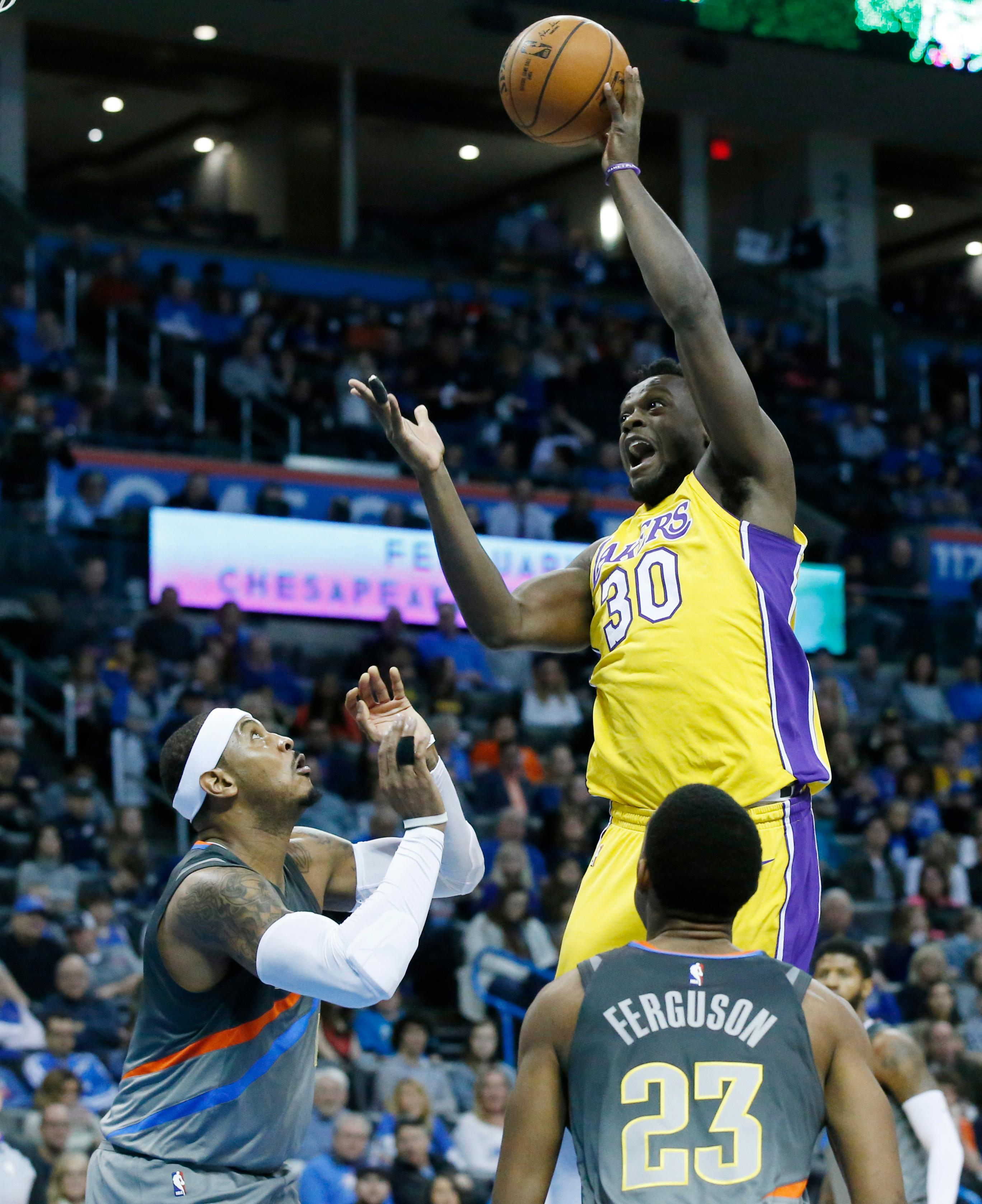 Los Angeles Lakers forward Julius Randle (30) shoots in front of Oklahoma City Thunder forward Carmelo Anthony, left, and guard Terrance Ferguson (23) in the first half of an NBA basketball game in Oklahoma City, Sunday, Feb. 4, 2018. (AP Photo/Sue Ogrocki)