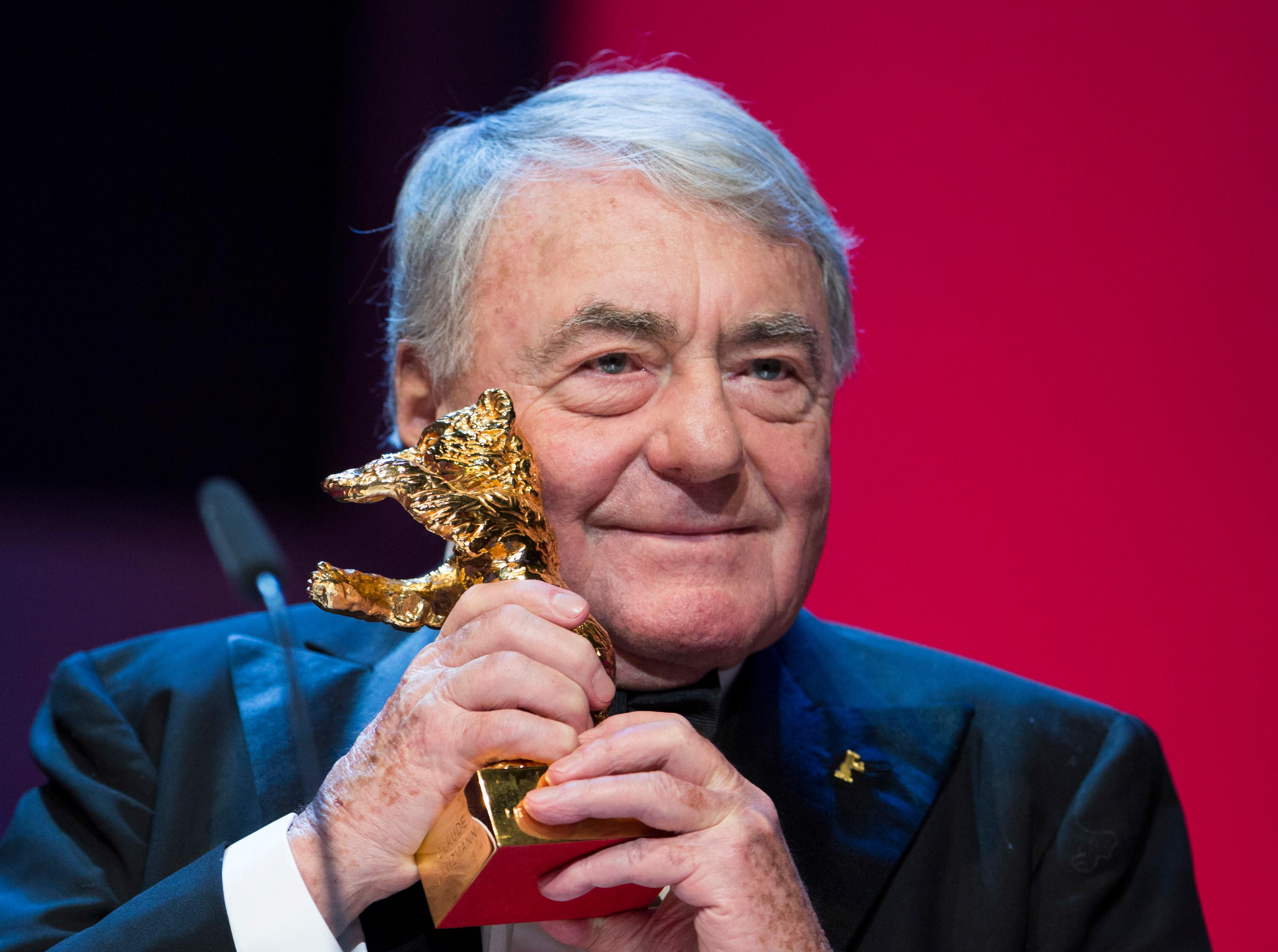 FILE - In this Feb.14, 2013 file photo, French film director Claude Lanzmann holds the Honorary Golden Bear at the 63rd edition of the Berlinale, International Film Festival in Berlin, Germany. Lanzmann, director of the epic movie 'Shoah,' has died at age 92 his publisher said Thursday, July 5, 2018. (AP Photo/Gero Breloer, File)