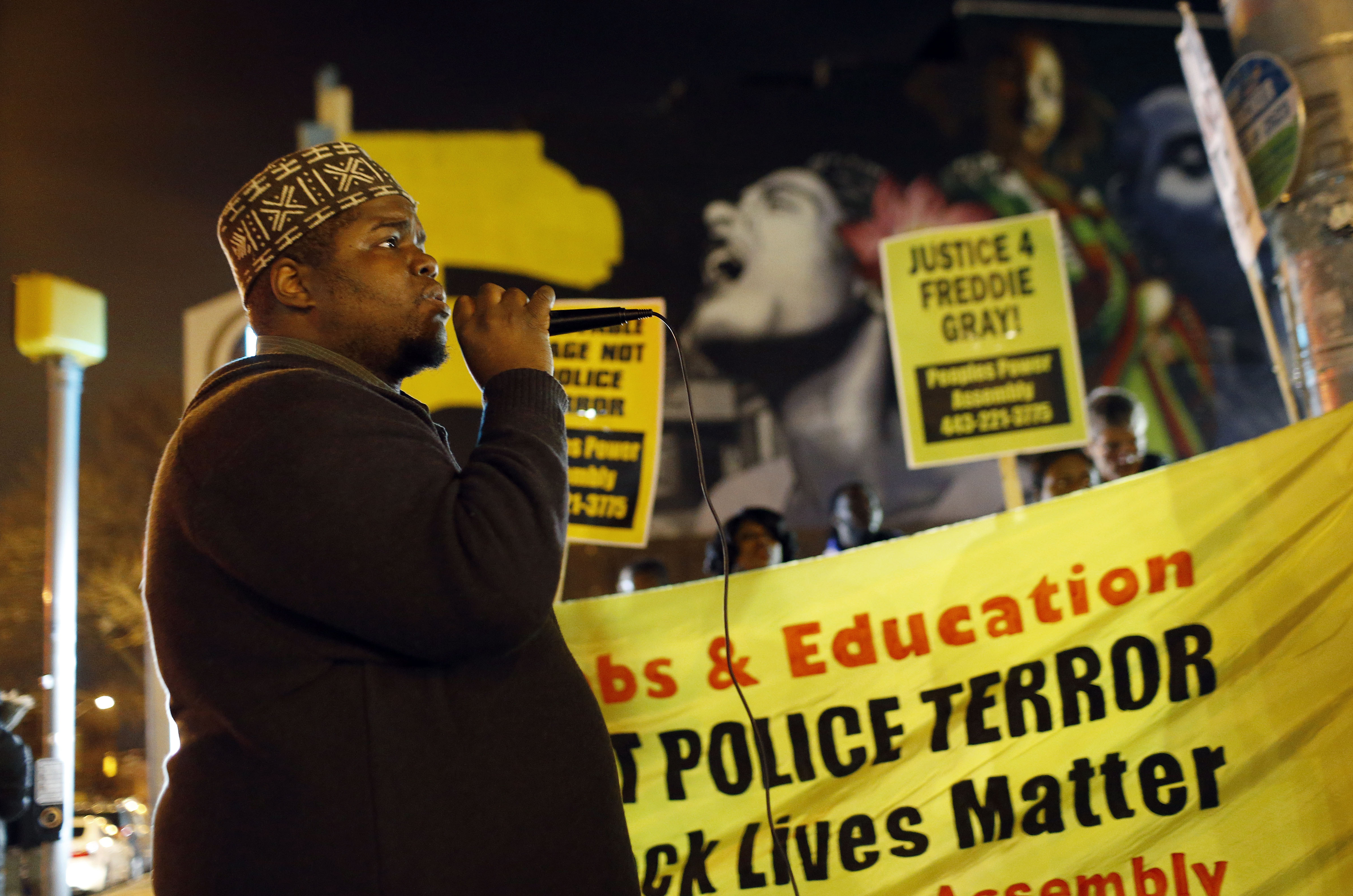 The Rev. C.D. Witherspoon speaks during a peaceful protest at the intersection of North and Pennsylvania Avenues, Wednesday, Dec. 16, 2015, in Baltimore, the site of unrest following the funeral of Freddie Gray. Peaceful protests took place in response to a hung jury and mistrial for Officer William Porter, one of six Baltimore city police officers charged in connection to Gray's death. (AP Photo/Patrick Semansky)