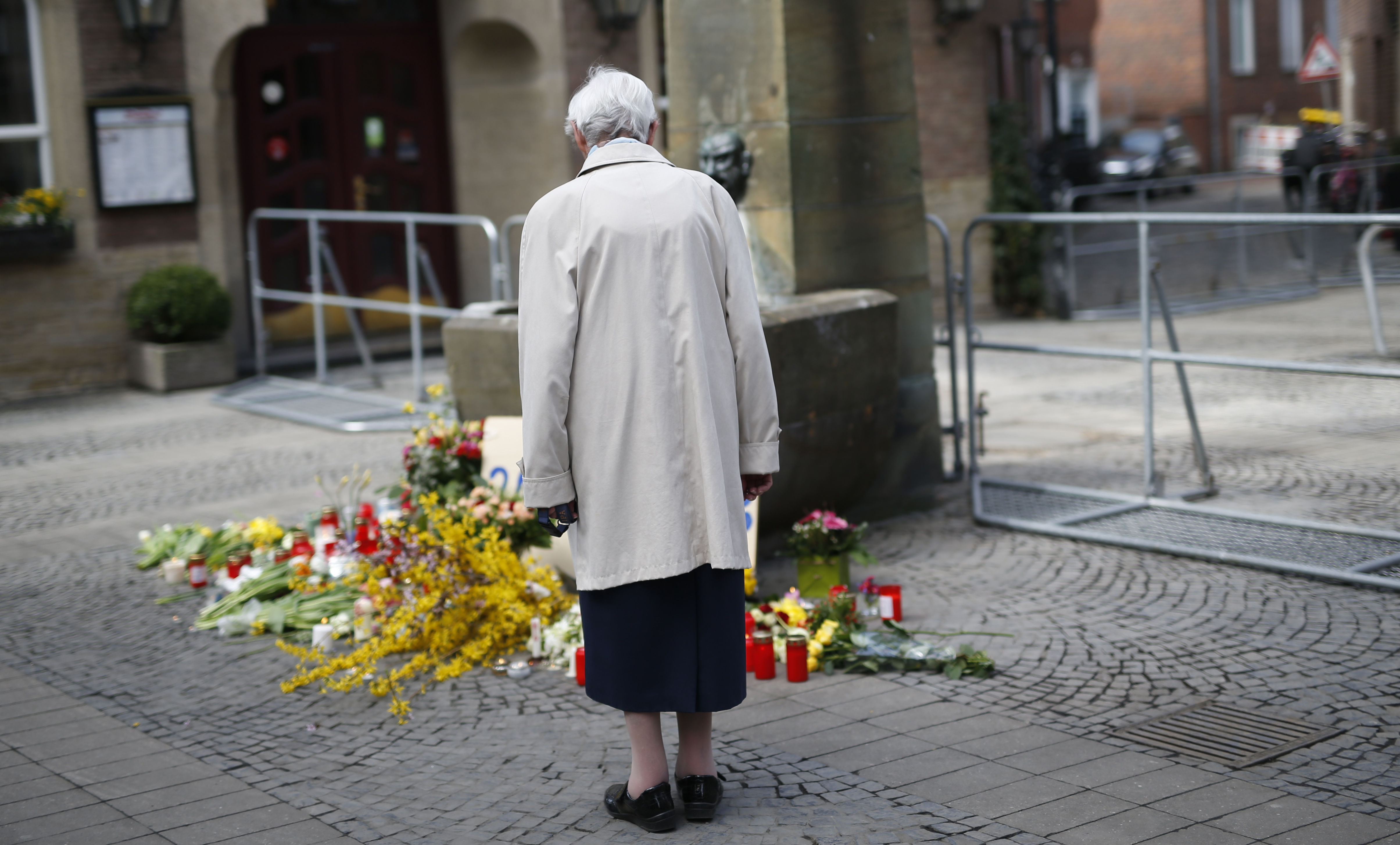 An elderly woman looks at flowers  in front of a fountain in Muenster, western Germany, Sunday, April 8, 2018, one day after a van crashed into people drinking outside the popular bar, killing two people and injuring 20 others before the driver of the vehicle shot and killed himself inside it. (Ina Fassbender/dpa via AP)