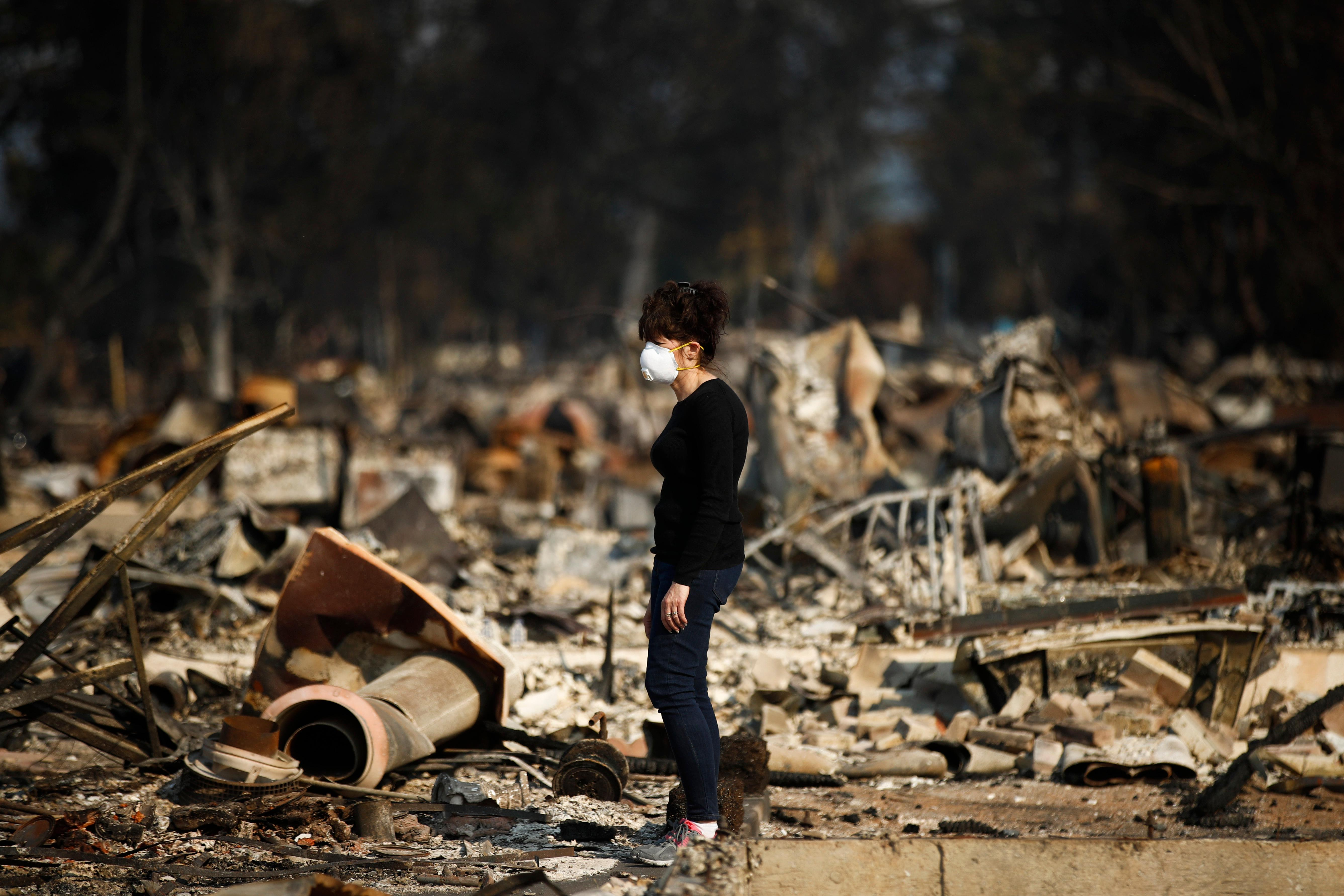 "Karen Curzon stands in what remains of her home, which was destroyed by a wildfire in the Coffey Park neighborhood, Sunday, Oct. 15, 2017, in Santa Rosa, Calif. ""We are going to rebound, rebuild and get this community back,"" said Curzon. (AP Photo/Jae C. Hong)"