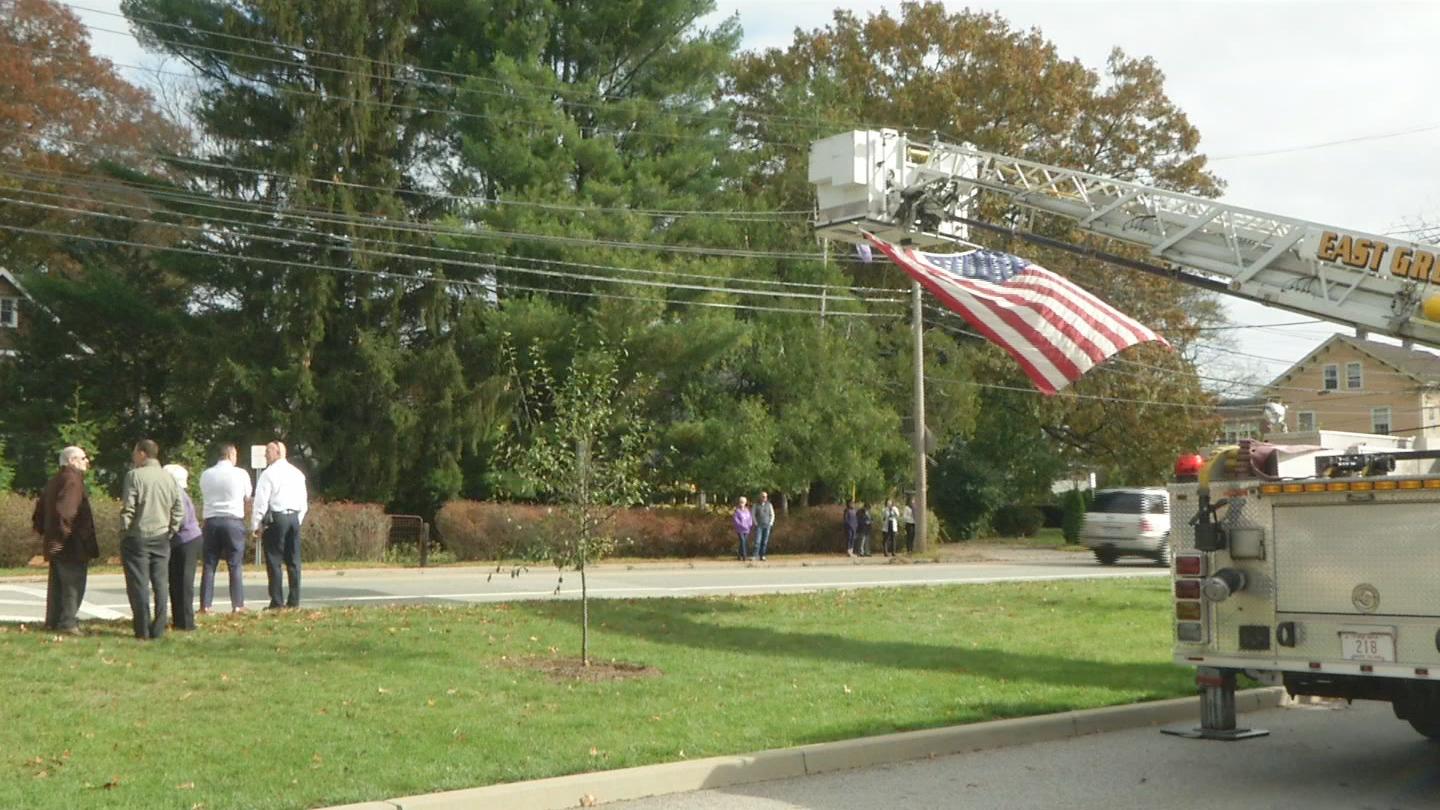 An American flag flies from a firetruck ladder at the East Greenwich Police Department. (WJAR)<p></p>