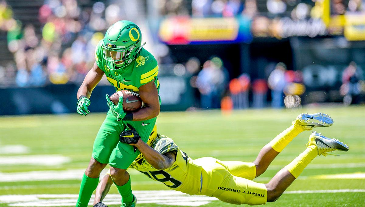 The Thunder's Jaylon Redd (#30) is brought down during a run by the Lightning's Billy Gibson (#28). The Thunder defeated the Lightning 59-24 in the Spring Game on Saturday at Autzen Stadium. Photo by August Frank