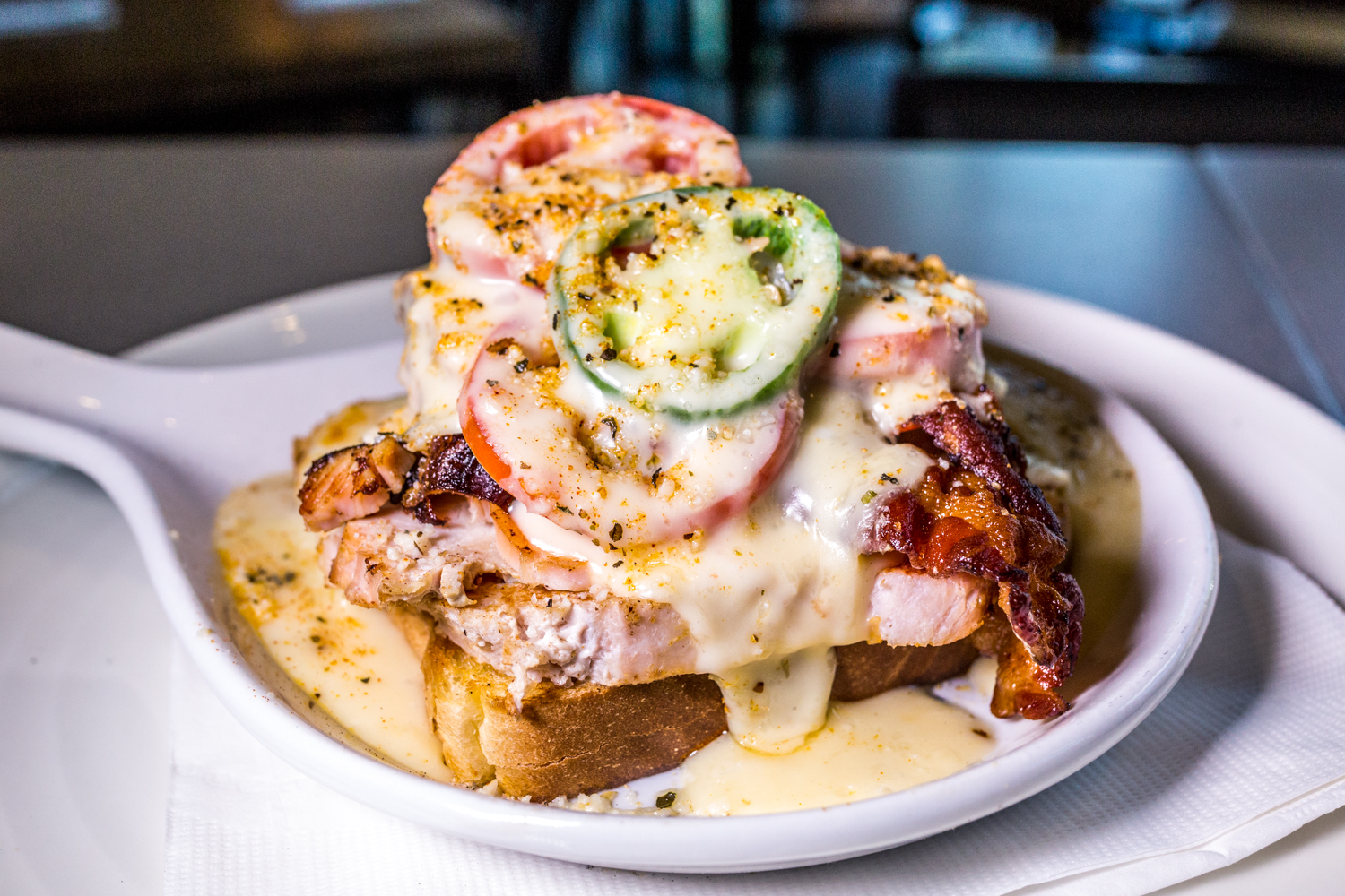 Covington's Own Hot Brown: buttery, thick-cut toast topped with smoked turkey, sliced Roma tomatoes, fresh jalapeño , applewood smoked bacon, covered in Mornay sauce, and then baked with pecorino romano cheese and Parlor Spice Blend / Image: Catherine Viox{ }// Published: 10.10.19