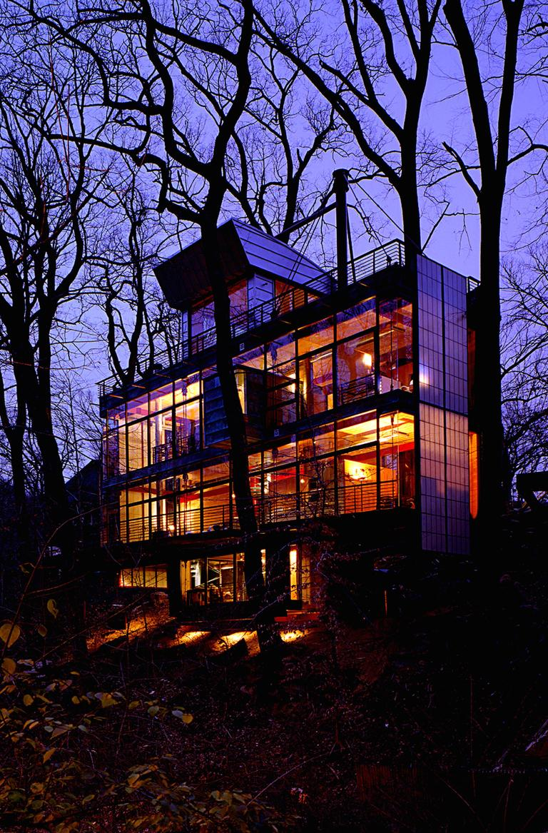 <p>The home is inspired by the simple and natural virtues of the site's trees and rock outcroppings. An abundance of trees splitting rocks near a stream bed are the essences of the Park running through the center of D.C. The home is seen as an abstracted tree with a street side of patina copper planted on two columns at the cliff's edge hung by steel cables. The park side rear is clad with transparent super-insulated glazing. Trees are saved and wrap through the house. The design desires to blend into the park by its matching natural colors as well as its use of glass which reflectively display the preserved trees surrounding it. (Image: Ken Wyner)</p><p></p>