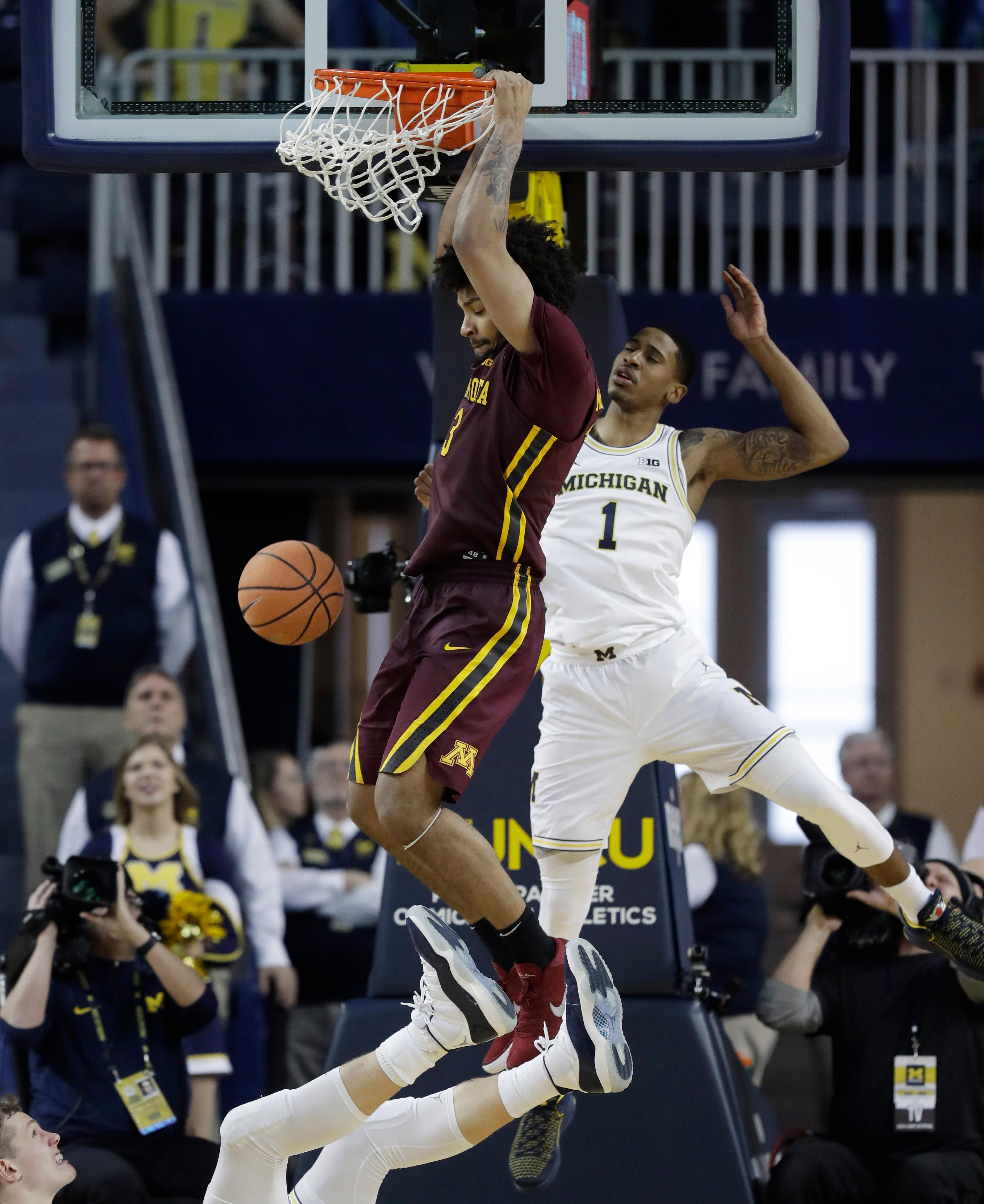 Minnesota forward Jordan Murphy (3) dunks as Michigan guard Charles Matthews (1) defends during the second half of an NCAA college basketball game, Saturday, Feb. 3,2018, in Ann Arbor, Mich. (AP Photo/Carlos Osorio)