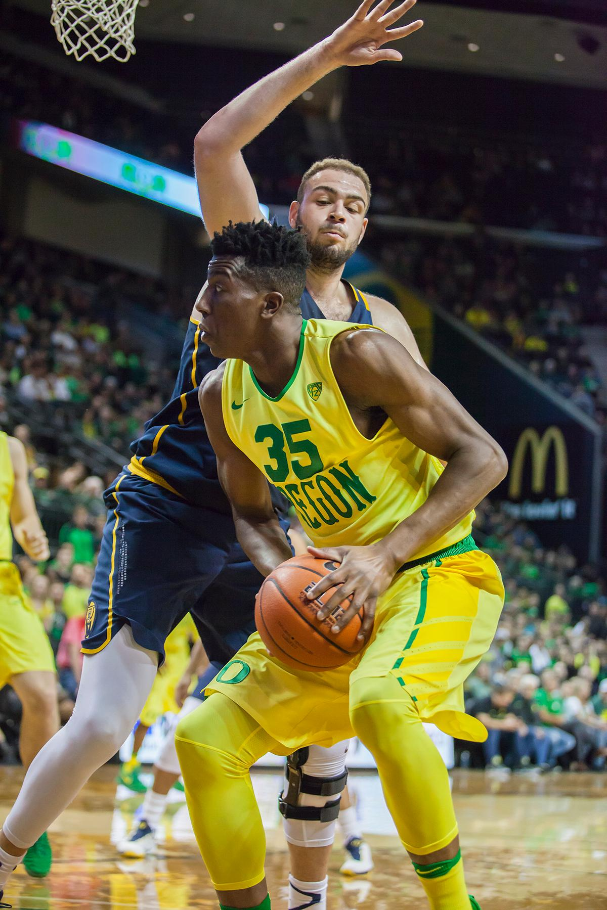 Oregon forward Kavell Bigby-Williams (#35) looks past California center Kameron Rooks (#44) for an unguarded teammate. The Oregon Ducks defeated the California Golden Bears 86 to 63. Photo by Ben Lonergan, Oregon News Lab