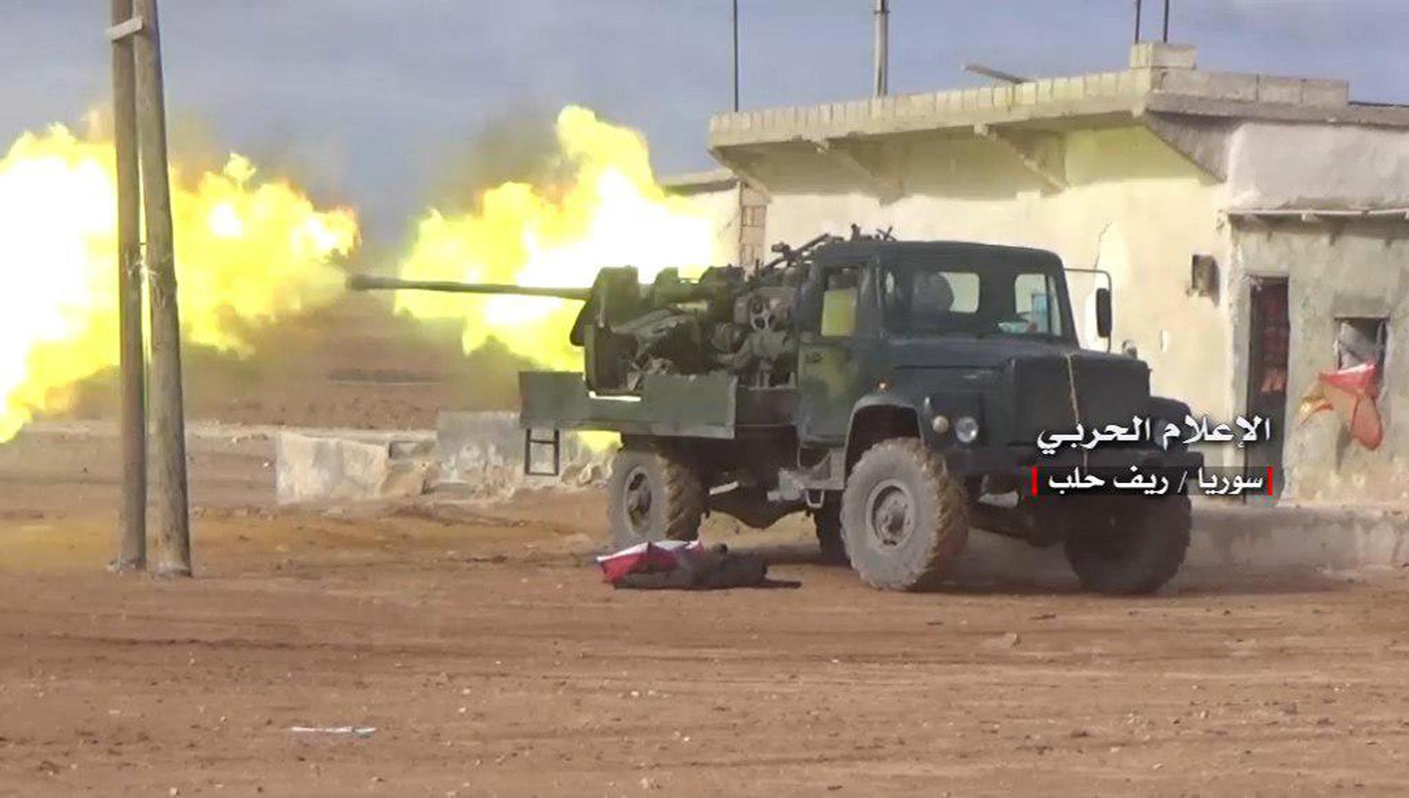 This photo provided on Saturday, Jan. 20, 2018, by the government-controlled Syrian Central Military Media, shows Syrian government forces firing  their weapon during a battle against the Syrian opposition fighters, in the southern Aleppo countryside, Syria. Syrian state TV says government forces have retaken a key air base in northwest Syria that was lost to rebels in 2015. The state broadcaster says Syrian troops fought their way into the strategic Abu Zuhour air base on Saturday, in Idlib province. (Syrian Central Military Media, via AP)