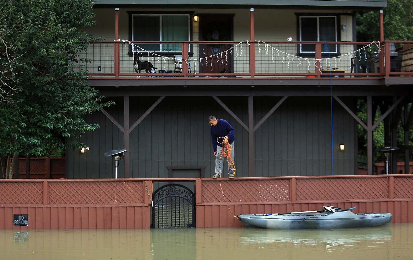 A resident of Guerneville, Calif., off River Road ties up a kayak to his property, as flood waters from the Russian River surround his home, Wednesday, Jan. 11, 2017. Dozens of Northern California residents have been rescued by boats and firetrucks from flooded homes near Hollister, California as a drought-busting series of storms moved out of the region. Days of rain and snow have toppled trees and forced people out of water-logged homes.   (Kent Porter/The Press Democrat via AP)