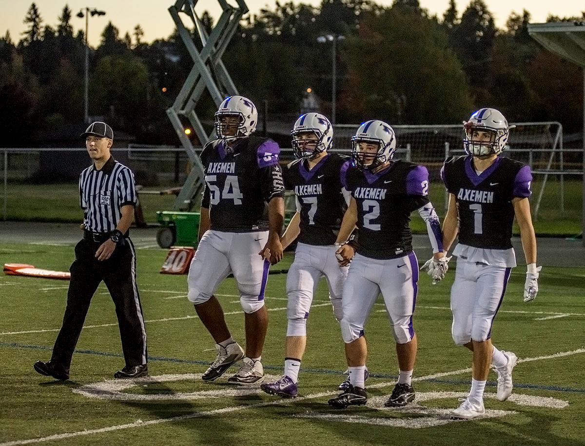 South Eugene Axemen quarterback Bryce Boettcher (#7), offensive lineman Jahi Richardson (#54) and wide receivers Elliot James (#1) and Jake Quinn (#2) walk onto the field for the coin toss.  The Sheldon Irish defeated the South Eugene Axemen 63-6 at South on Friday night. Photo by Abigail Winn, Oregon News Lab