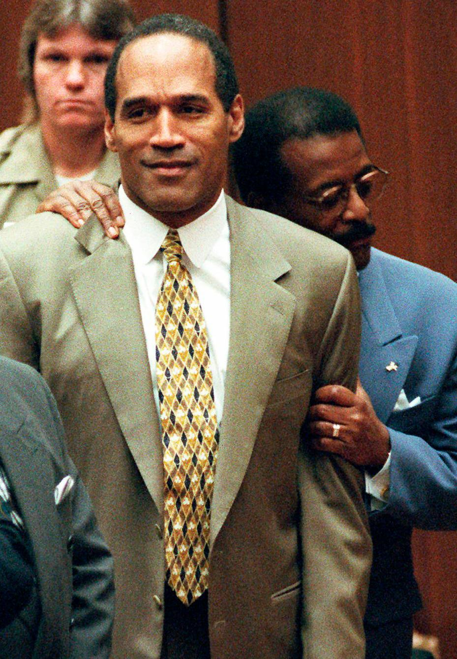 FILE - In this Oct. 3, 1995 file photo, attorney Johnnie Cochran Jr., right, holds onto O.J. Simpson as the not guilty verdict is read in a Los Angeles courtroom. Simpson, the former football star, TV pitchman and now Nevada prison inmate, will have a lot going for him when he appears before state parole board members Thursday, July 20, 2017, seeking his release after more than eight years for an ill-fated bid to retrieve sports memorabilia. (AP Photo/Pool, Myung J. Chun, file)
