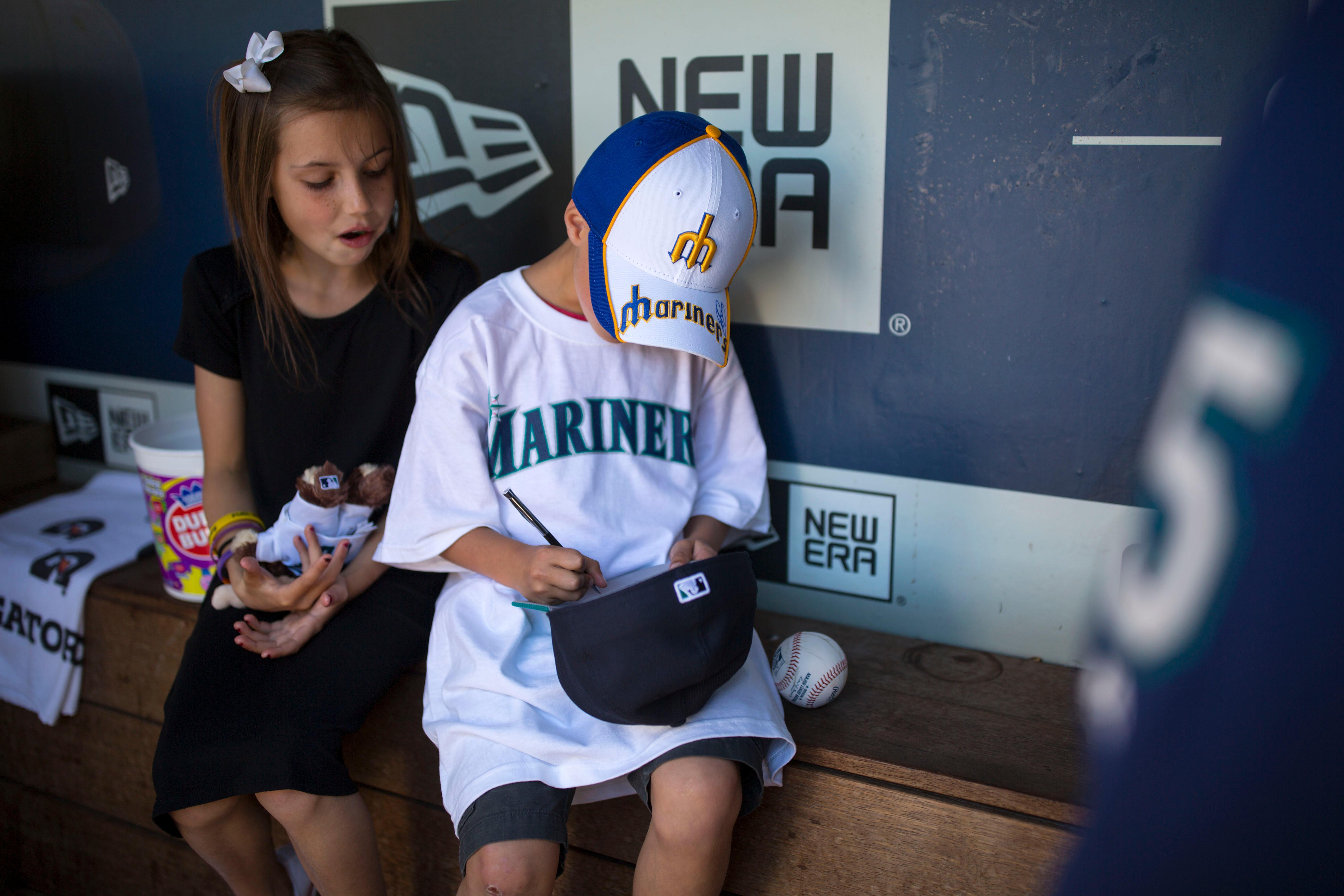 "Seven-year-old kidney cancer survivor Mason Nettleton signs Seattle Mariner Kyle Seager's hat as Nettleton served Seattle as a ""Superhero for a Day"" on Tuesday, June 27, 2017. (Sy Bean/ Seattle Refined)"