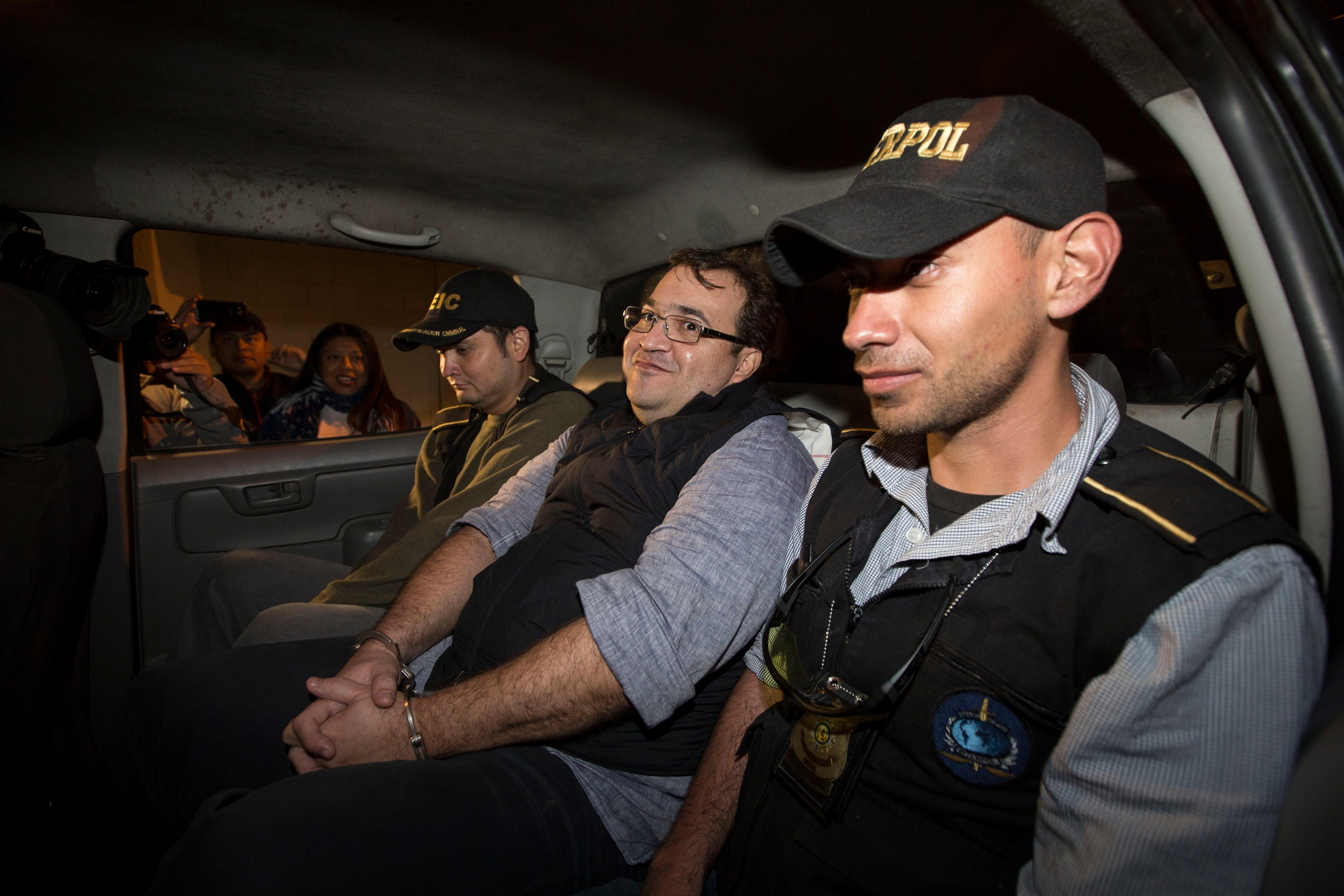 Mexico's former Veracruz state Gov. Javier Duarte, center, is escorted by agents of the local Interpol office inside a police car as they arrive at Guatemala City, early Sunday, April 16, 2017. Duarte, who is accused of running a ring that allegedly pilfered from state coffers, has been detained in Guatemala after six months as a fugitive and a high-profile symbol of government corruption. (AP Photo/Moises Castillo)
