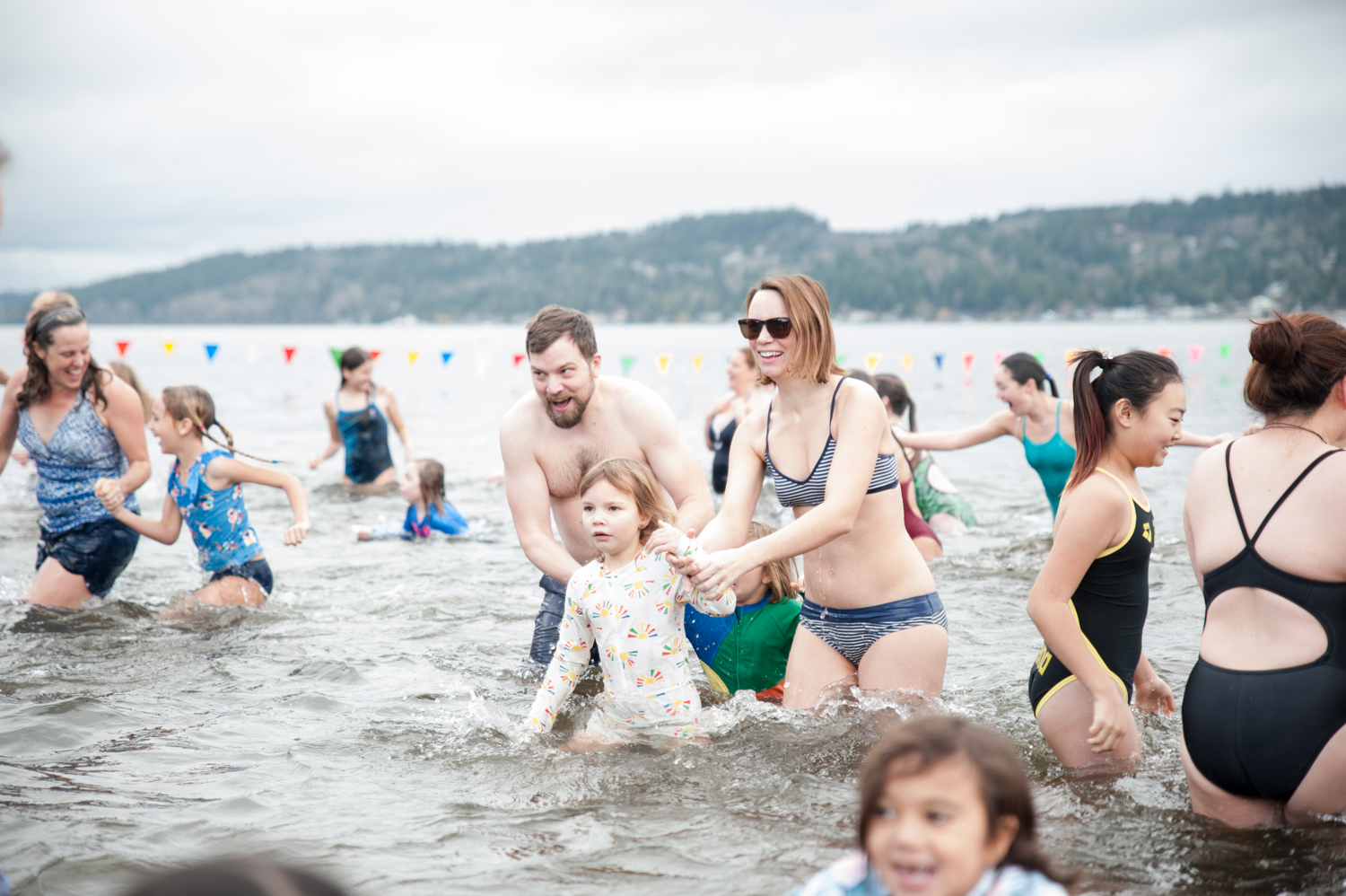 Happy New Year! How are you spending the first day of 2020? Thousands of people spent it in the freezing cold waters of Lake Washington at high noon exactly, as part of the annual Polar Bear Plunge. Costumes were encouraged as participants gathered at Matthews Beach beforehand, and had warm refreshments waiting for them afterwards! Limited Badges of Courage were awarded to those who darned to fully submerge…..HAPPY 2018! January 1, 2020. (Image: Elizabeth Crook / Seattle Refined)