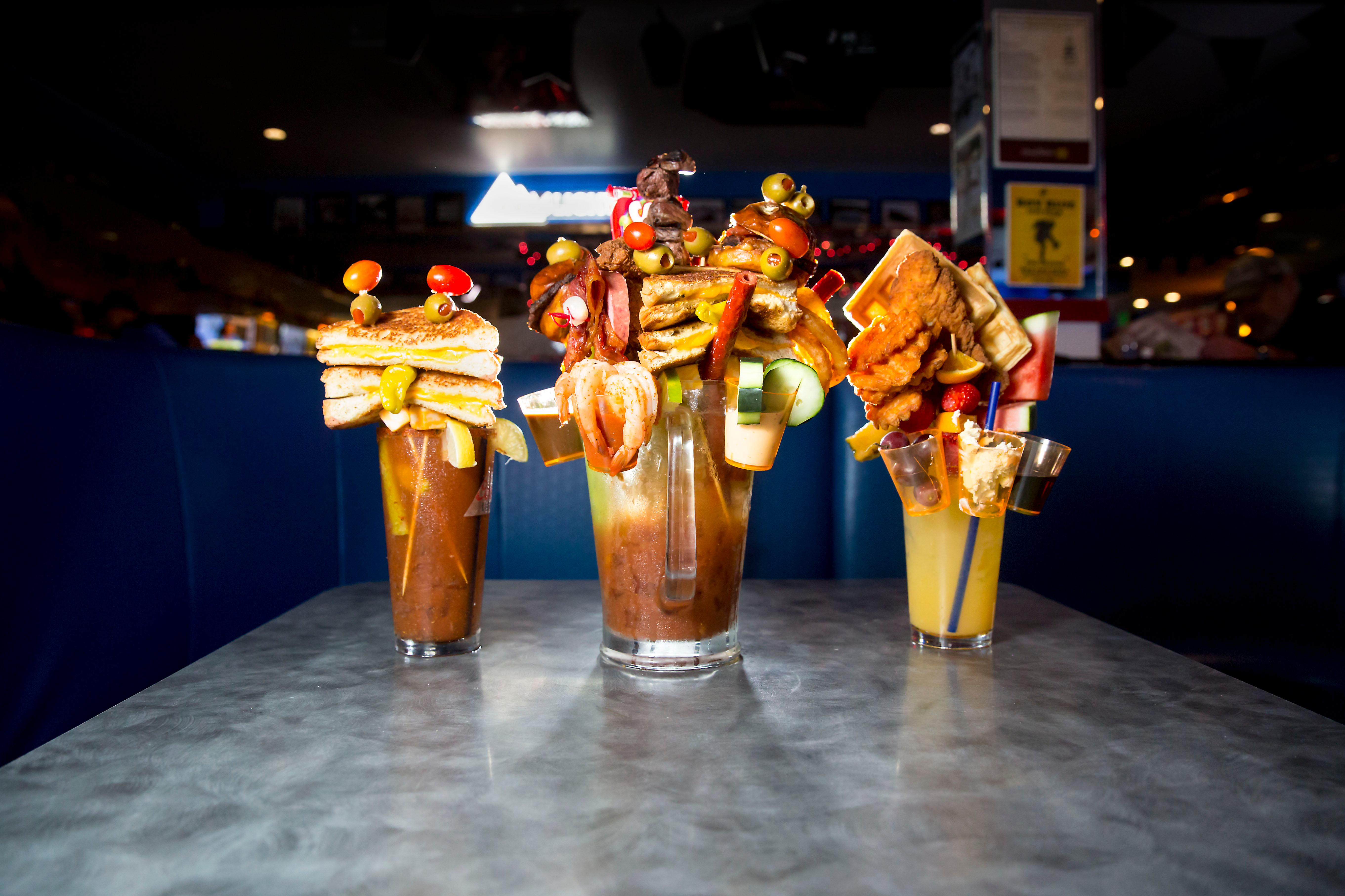 The Southern Bloody Mary (Chicken and Waffles, 22oz Manmosa Base), The Grilled Cheese (22oz Bloody Mary with Grilled Cheese Sandwich and the Big Mother Mary (Full pitcher of bloody mary, grilled cheese sandwich, steak bites, ribs, salami, olives, sliders, onion rings, shrimp cocktail, fried shrimp, cucumber, candied bacon bows, and meat stick straws). The Big Mother Mary HAS to be shared by two people. The Garage Bar & Grill in Bremerton, WA. (Sy Bean / Seattle Refined)