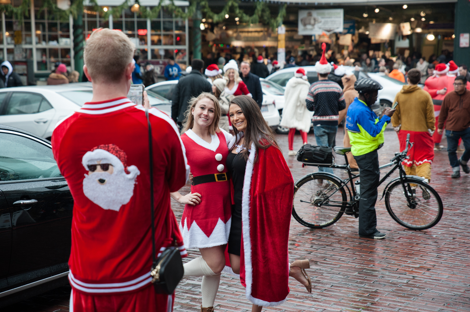 "Thousands of Santas flooded the streets of Seattle for the annual Seattle Santa Con. Hundreds of people packed bars downtown in Santa, Elf and Reindeer attire. The focus is on spontaneity and creativity, while having a good time and spreading cheer and goodwill. and their #1 rule? ""My name is Santa. Your name is Santa. We are Santa. Who's in charge here? Santa!"" (Image: Elizabeth Crook / Seattle Refined)"