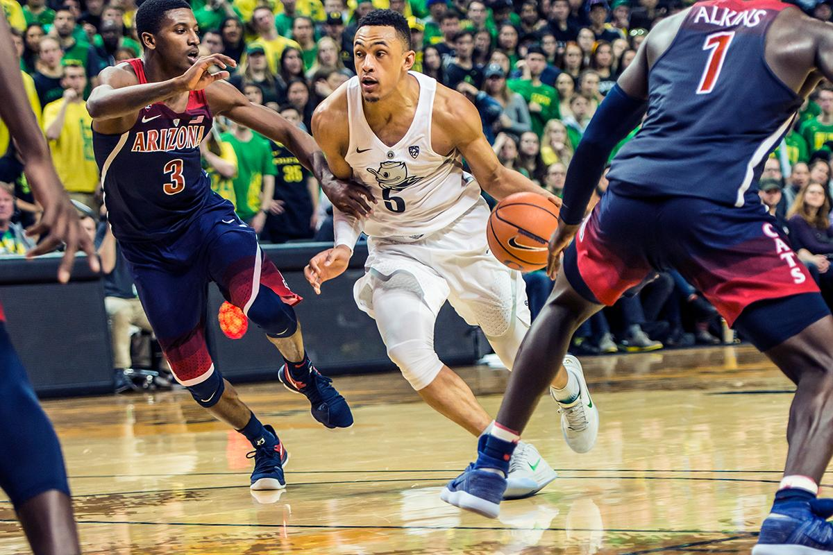 Oregon's Elijah Brown drives against Arizona defenders in their matchup at Matthew Knight Arena Saturday. The Ducks upset the fourteenth ranked Wildcats 98-93 in a stunning overtime win in front of a packed house of over 12,000 fans for their final home game to improve to a 19-10 (9-7 PAC-12) record on the season. Oregon will finish out regular season play on the road in Washington next week against Washington State on Thursday, then Washington on the following Saturday. (Photo by Colin Houck)